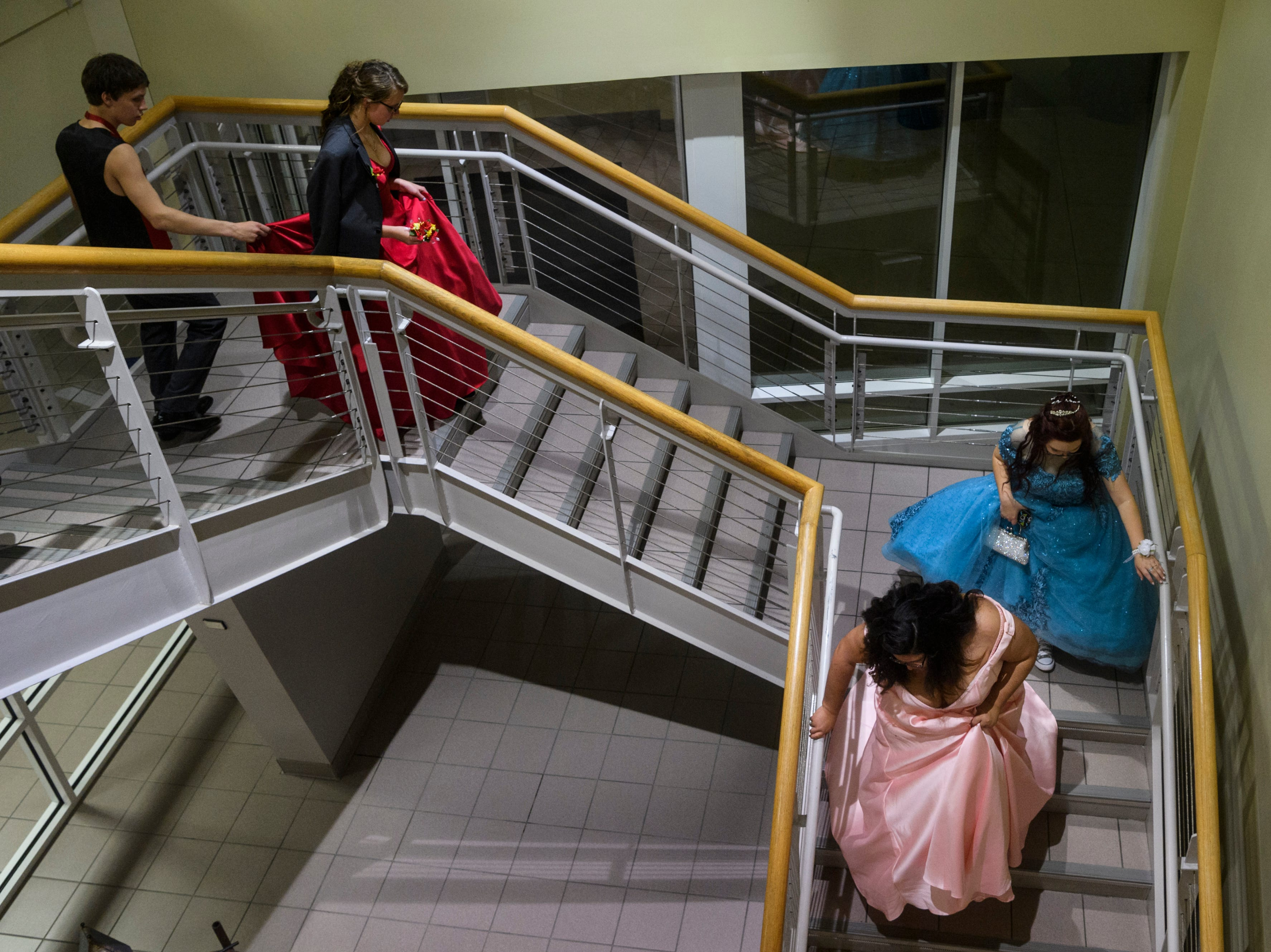 Felicitie Flemmings, from bottom, and Alexis Adamaitis carefully walk down the stairs followed by other prom goers once the dance was over at University of Southern Indiana in Evansville, Ind., Saturday, May 4, 2019.
