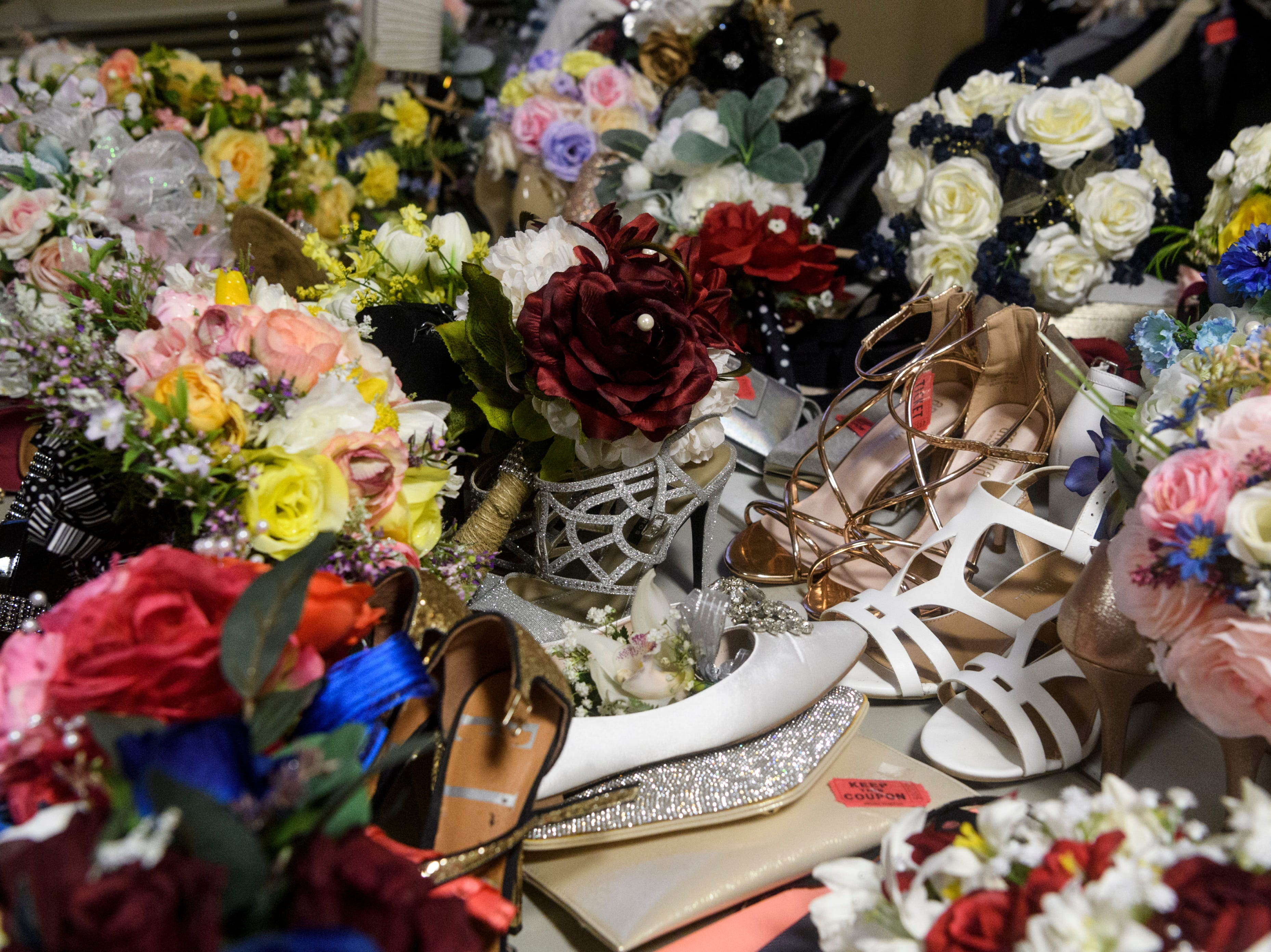 An assortment of bouquets, purses and shoes are left in a small coat check area away from the dance floor during North Posey's prom held at the Ribeyre Center in New Harmony, Ind., Saturday, May 4, 2019.