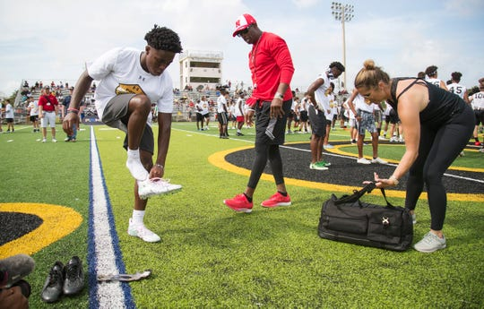 Miles Weston, left, puts on a pair of Deion Sanders', center, football cleats after his tore apart at the Prime Elite Underclassmen Football Camp on Sunday at Bishop Verot in Fort Myers. More than 700 middle and high school athletes attended the the camp that was put on by Under Armour and Deion Sanders.