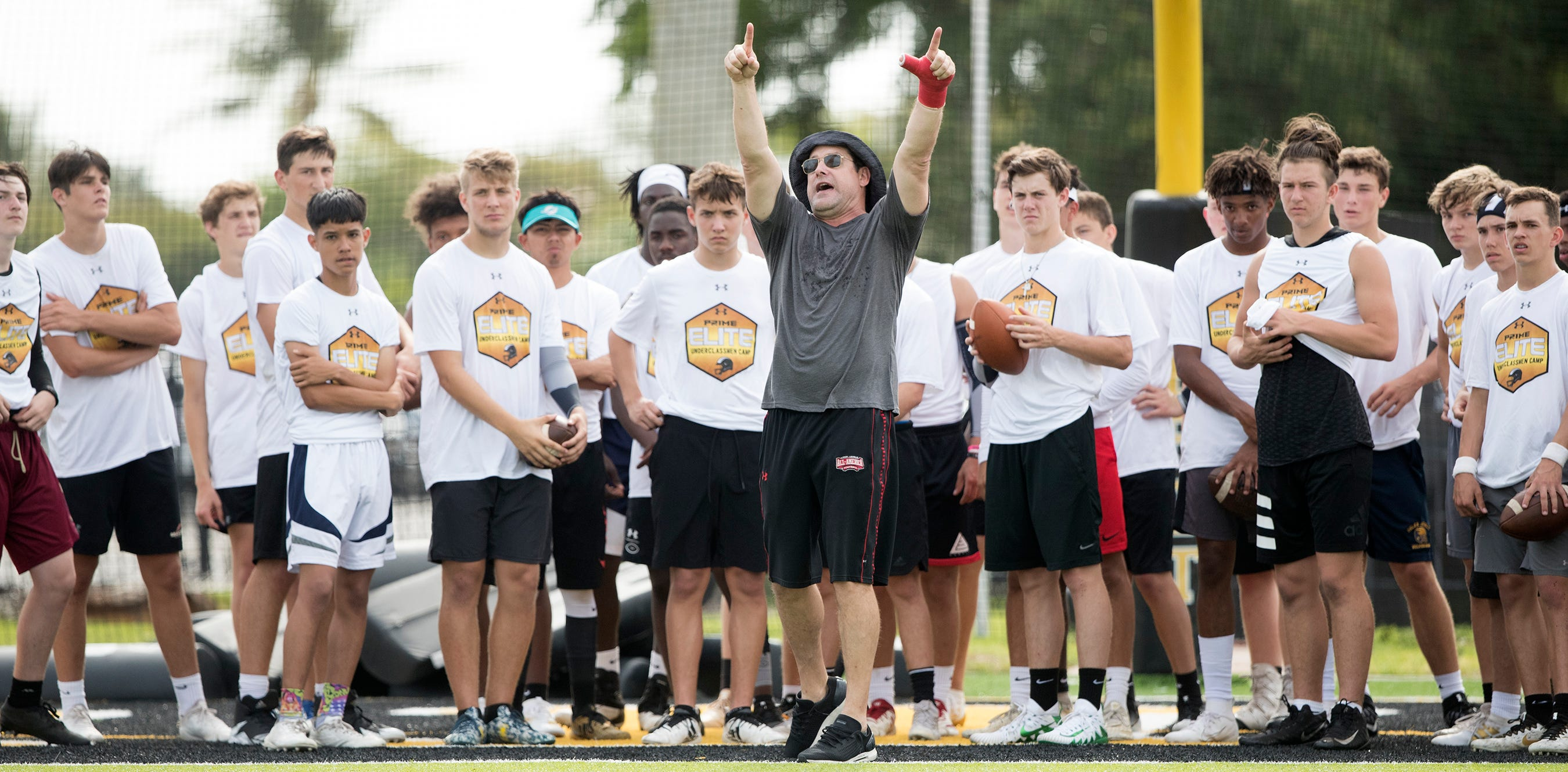 Tom Luginbill, center, ESPN National Recruiting Director, helps lead the Prime Elite Underclassmen Football Camp on Sunday at Bishop Verot in Fort Myers. More than 700 middle and high school athletes attended the camp that was put on by Under Armour and Deion Sanders.