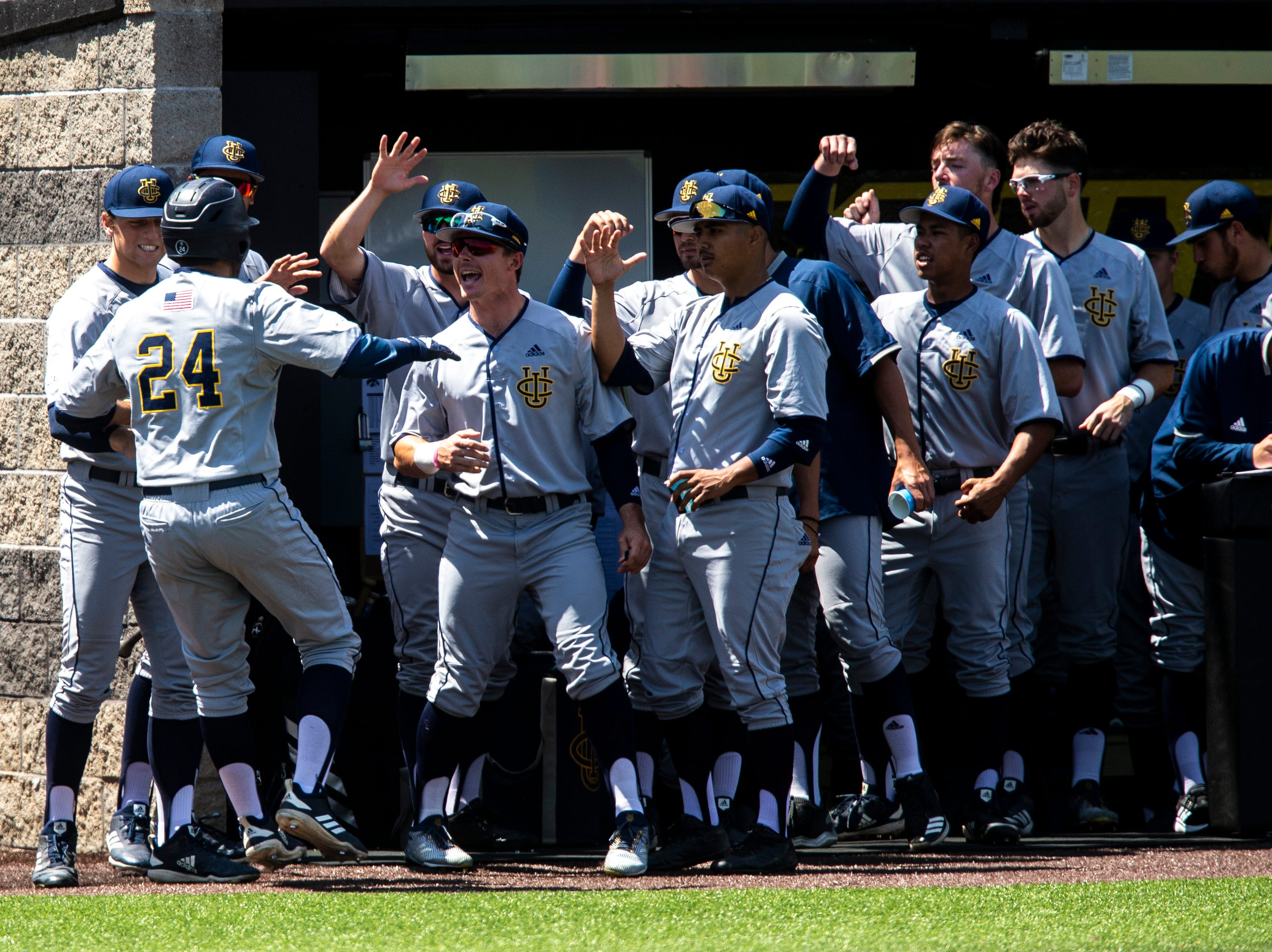 University of California Irvine's Jacob Castro (24) gets embraced by teammates after scoring a run during a NCAA non conference baseball game, Sunday, May 5, 2019, at Duane Banks Field in Iowa City, Iowa.