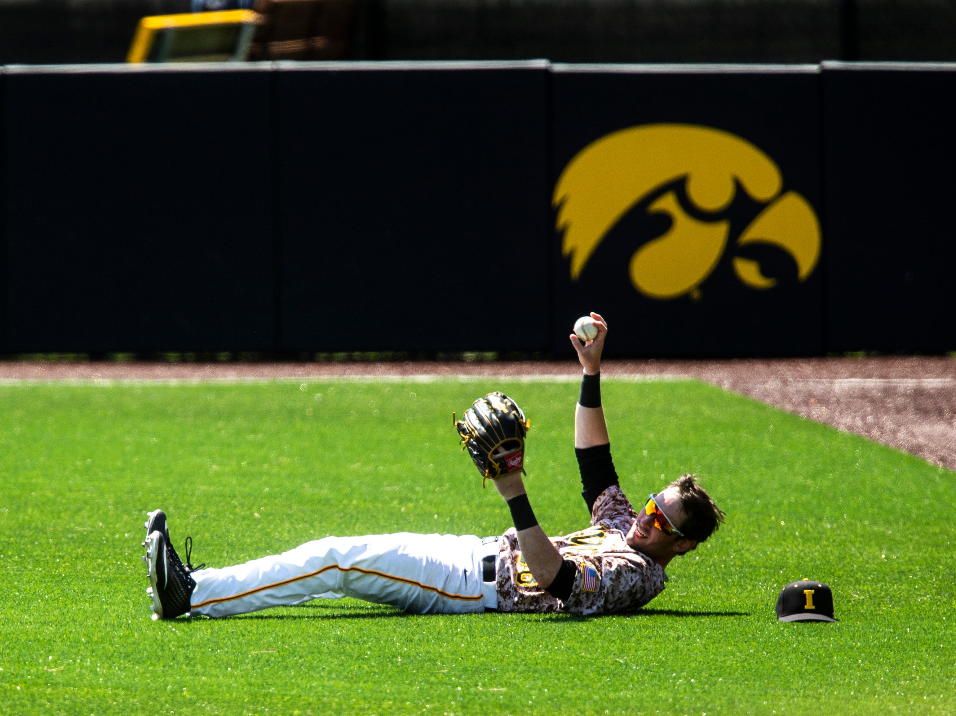 Iowa's Chris Whelan (28) holds up a ball after he made a leaping save in left field during a NCAA non conference baseball game, Sunday, May 5, 2019, at Duane Banks Field in Iowa City, Iowa.
