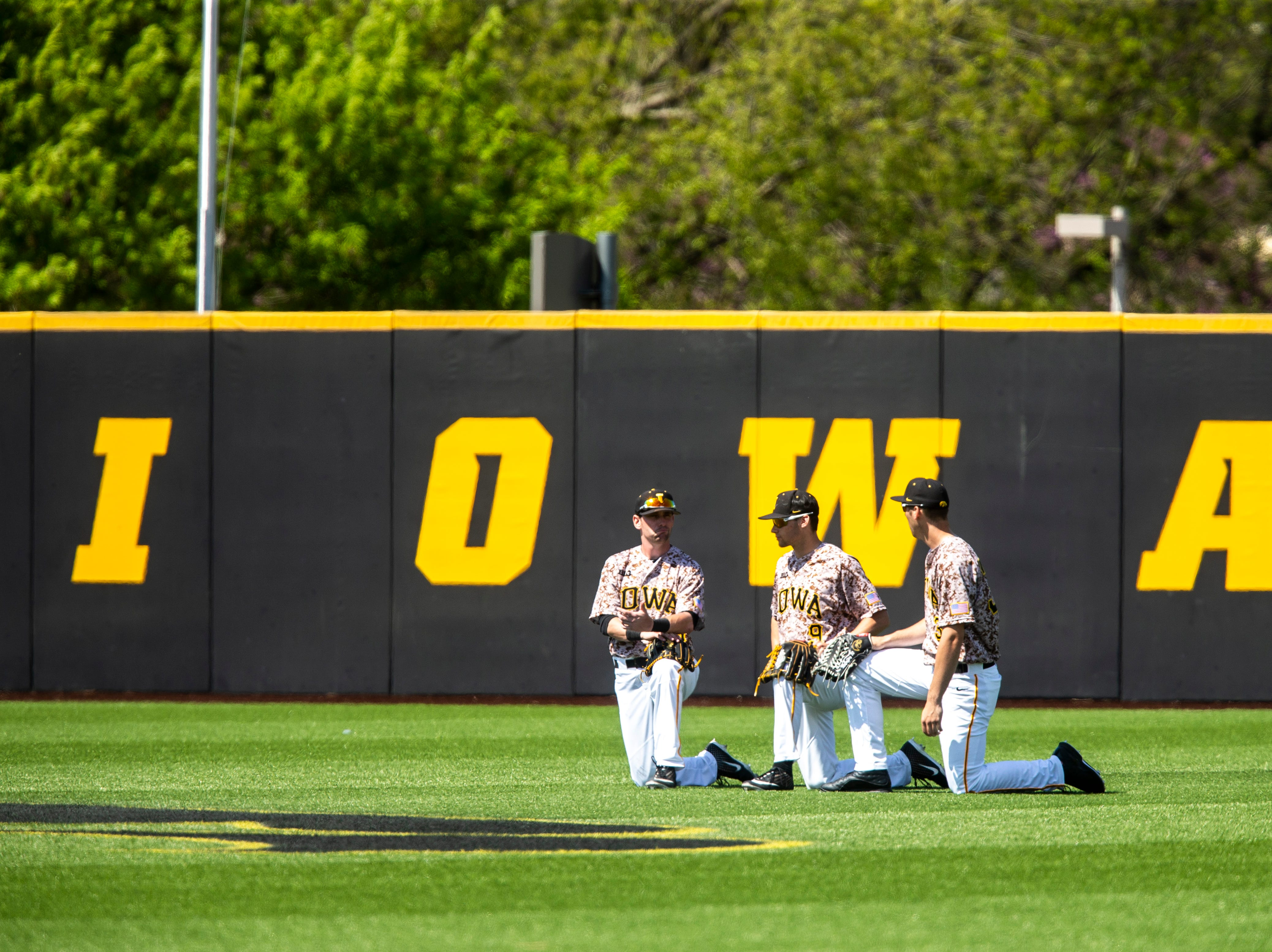 Iowa's Chris Whelan, from left, Ben Norman and Connor McCaffery kneel in the outfield during a NCAA non conference baseball game, Sunday, May 5, 2019, at Duane Banks Field in Iowa City, Iowa.