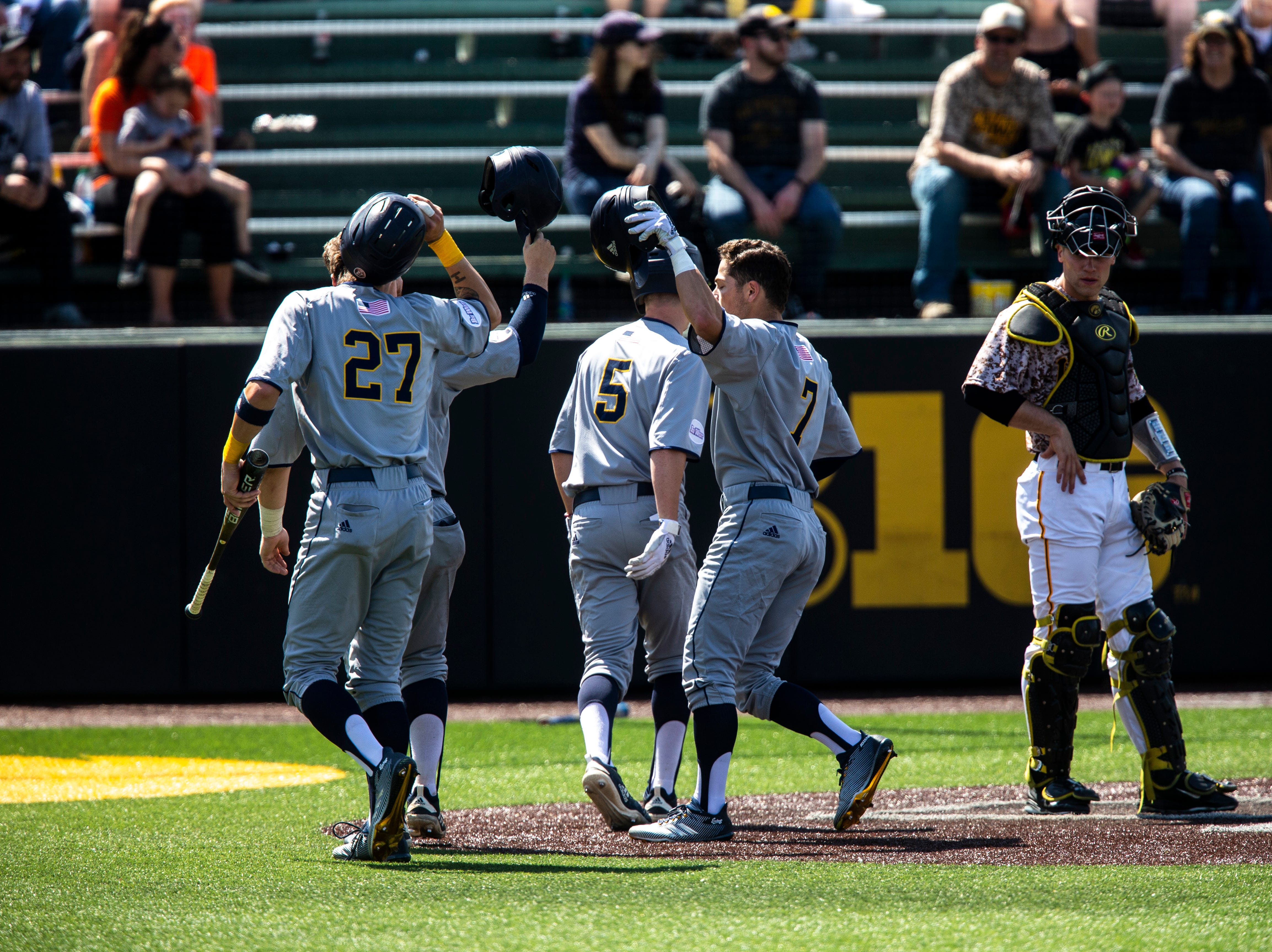 Iowa catcher Austin Martin, right, watches as University of California Irvine's Mikey Filia (7) celebrates with teammate Christian Koss (27) after scoring a run during a NCAA non conference baseball game, Sunday, May 5, 2019, at Duane Banks Field in Iowa City, Iowa.