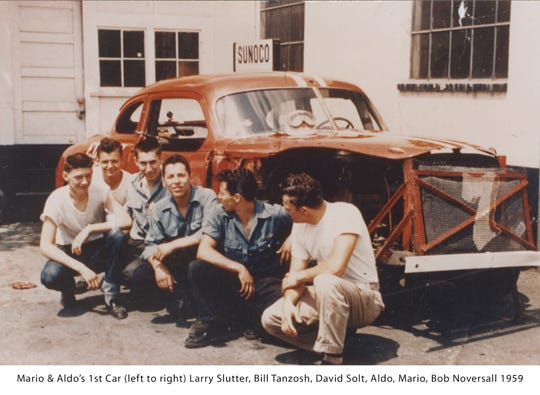 Mario Andretti, his brother Aldo and their friends pose in front of the first car the Andrettis ever built and raced. From left to right are Larry Slutter, Bill Tanzosh, David Solt, Aldo, Mario and Bob Noversall.