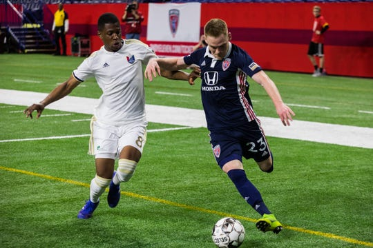 Indy Eleven's Tyler Pasher makes his way around North Carolina defense, Dre Fortune, and toward the goal during the team's 0-0 match against North Carolina FC at Lucas Oil Stadium on Saturday.
