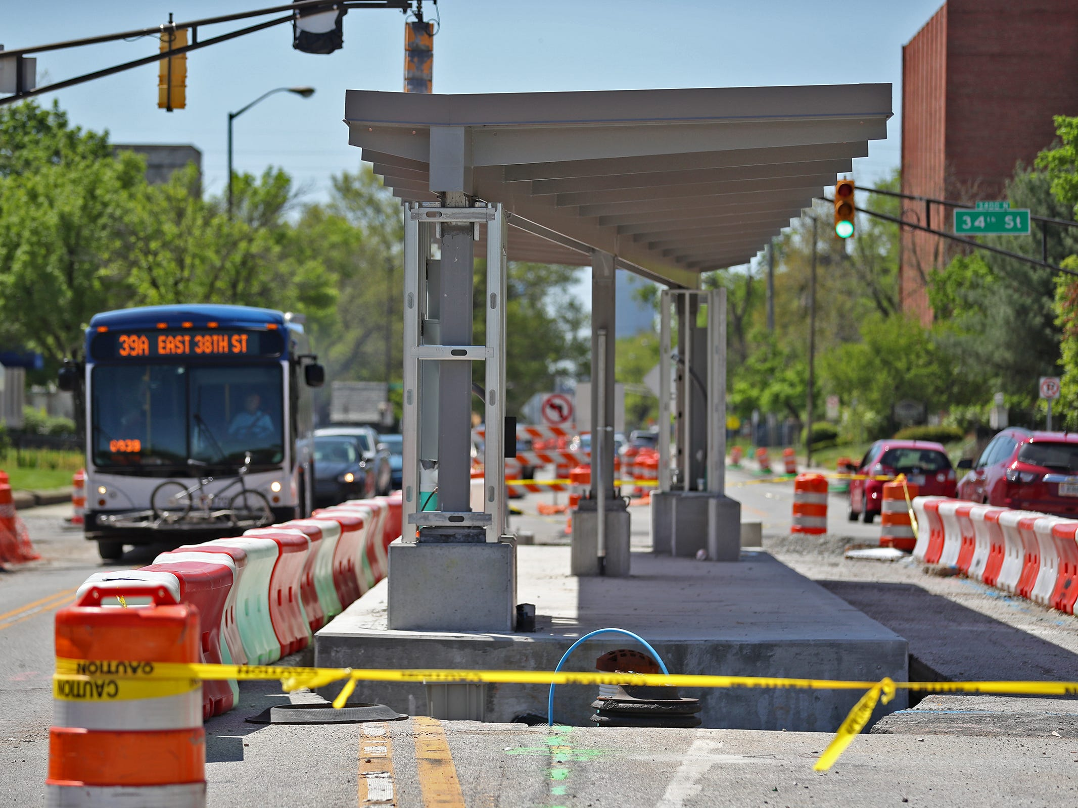 A bus heads north in the 3400 block of Meridian St. by a Red Line station construction site, Sunday, May 5, 2019.  The City has updated the timeline when the Red Line Bus Rapid Transit system should open, which is later in 2019 summer.
