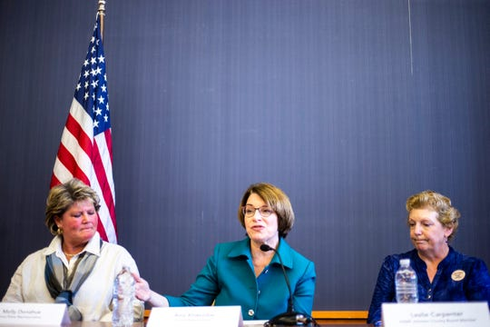 U.S. Sen. Amy Klobuchar, D-Minn., speaks during a round table discussion on mental health and addiction, Saturday, May 4, 2019, at the Public Library in Iowa City, Iowa. Iowa Rep. Molly Donahue, at left, and Leslie Carpenter, right.