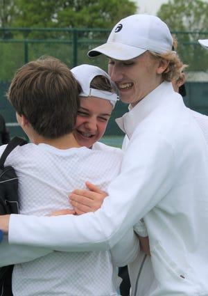 Tommy Secrist (center, facing camera) and repeat league MVP Benton Drake embrace Ross Drlik after he and doubles partner Evan Matney win a second set tiebreaker to complete a five-match sweep as Lexington repeats as Ohio Cardinal Conference tennis champion.