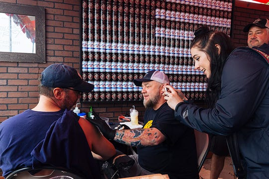 Father and daughter Stanley and Alexa Whitney are tattooed by Brent Hale of Bluff City Tattoos during the Sailor Jerry free tattoo giveaway at the 2019 Beale Street Music Festival at Tom Lee Park.