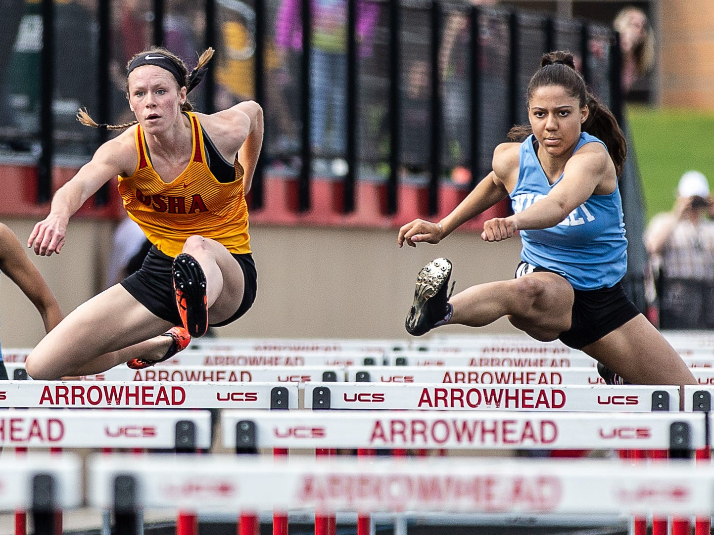 Divine Savior Holy Angels junior Jadin O'Brien (left) and Nicolet senior Destiny Huven compete in the 100 meter hurdles at the 2019 Myrhum Invitational track and field meet in Hartland on Saturday, May 4. O'Brien won with a time of 14.28.