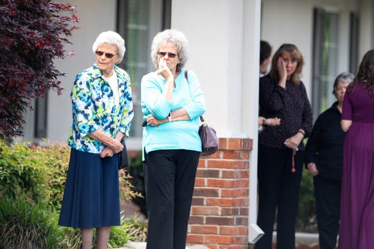 People watch the procession after Marsha Nuckols, 64, Rachel McGlothlin-Pee, 43, and her daughter Sapphire McGlothlin-Pee's, 12, funeral services at Gilbert Funeral Home Sunday, May 5, 2019, in Portland, Tenn.