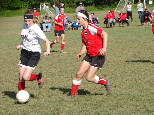 Mayci Sayre, of U15 XTABI, attempts to maneuver around a Columbus United defender Sunday during the championship match of the Buckeye Cup. XTABI won 4-1 at Alford-Reese Park.