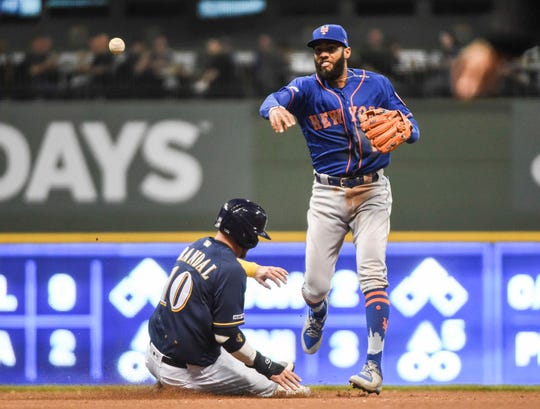 May 4, 2019; Milwaukee, WI, USA; New York Mets shortstop Amed Rosario (1) completes a double play after forcing out Milwaukee Brewers catcher Yasmani Grandal (10) in the sixth inning  at Miller Park.