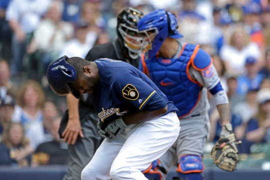 Milwaukee Brewers' Lorenzo Cain, front, reacts after being hit by a pitch during the sixth inning of a game against the New York Mets, Sunday, May 5, 2019, in Milwaukee. Cain was taken out of the game.