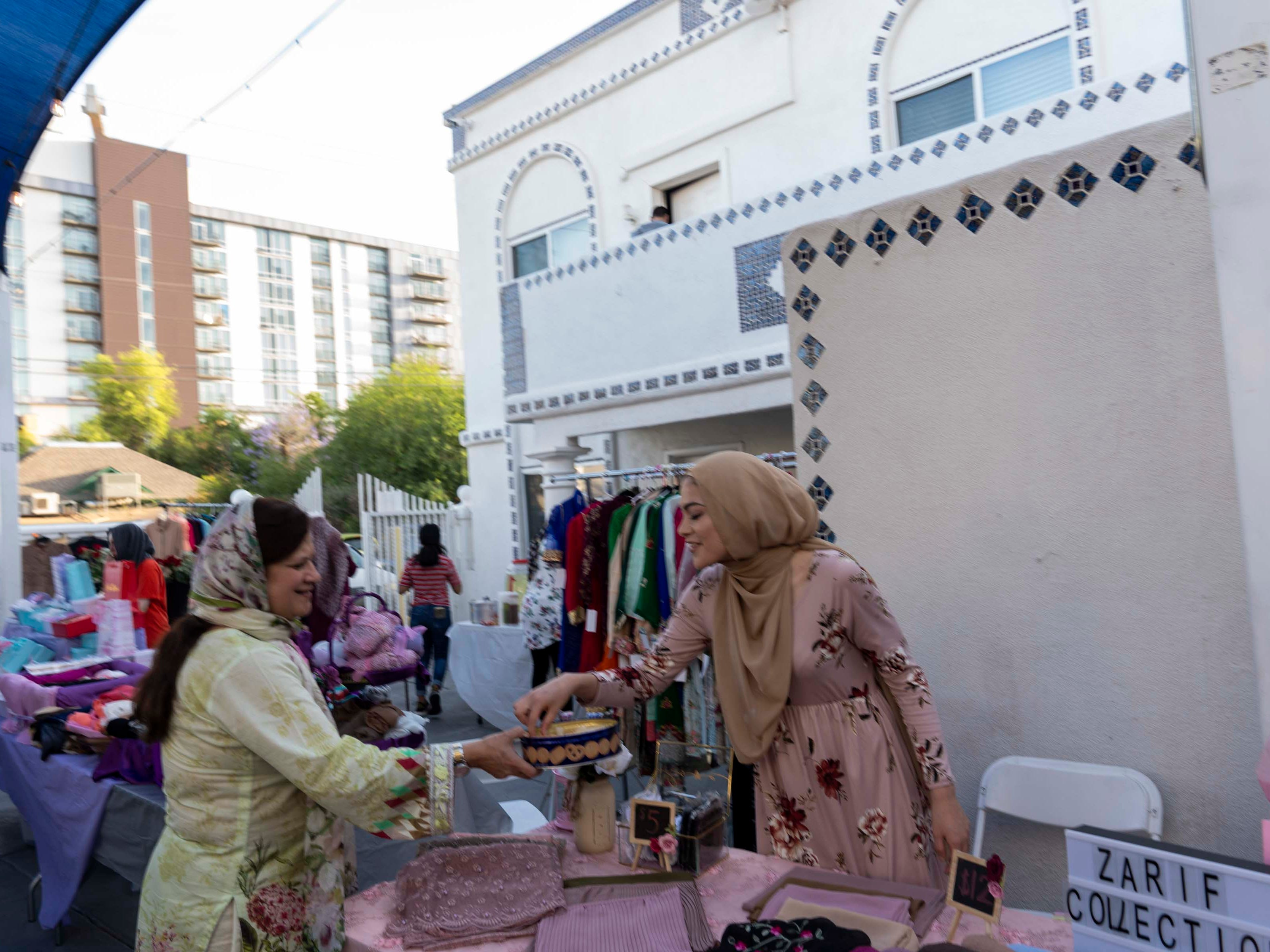 Fehmida Khamisani, on left, share sweets while she sells clothing to the Muslim community for Ramadan at Tempe Islamic Cultural Center.