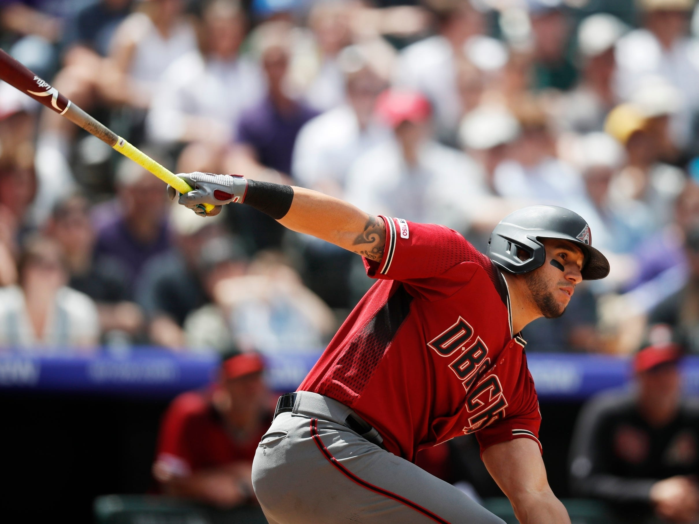 Arizona Diamondbacks' David Peralta follows the flight of his RBI-double off Colorado Rockies starting pitcher German Marquez in the third inning of a baseball game Sunday, May 5, 2019, in Denver. (AP Photo/David Zalubowski)