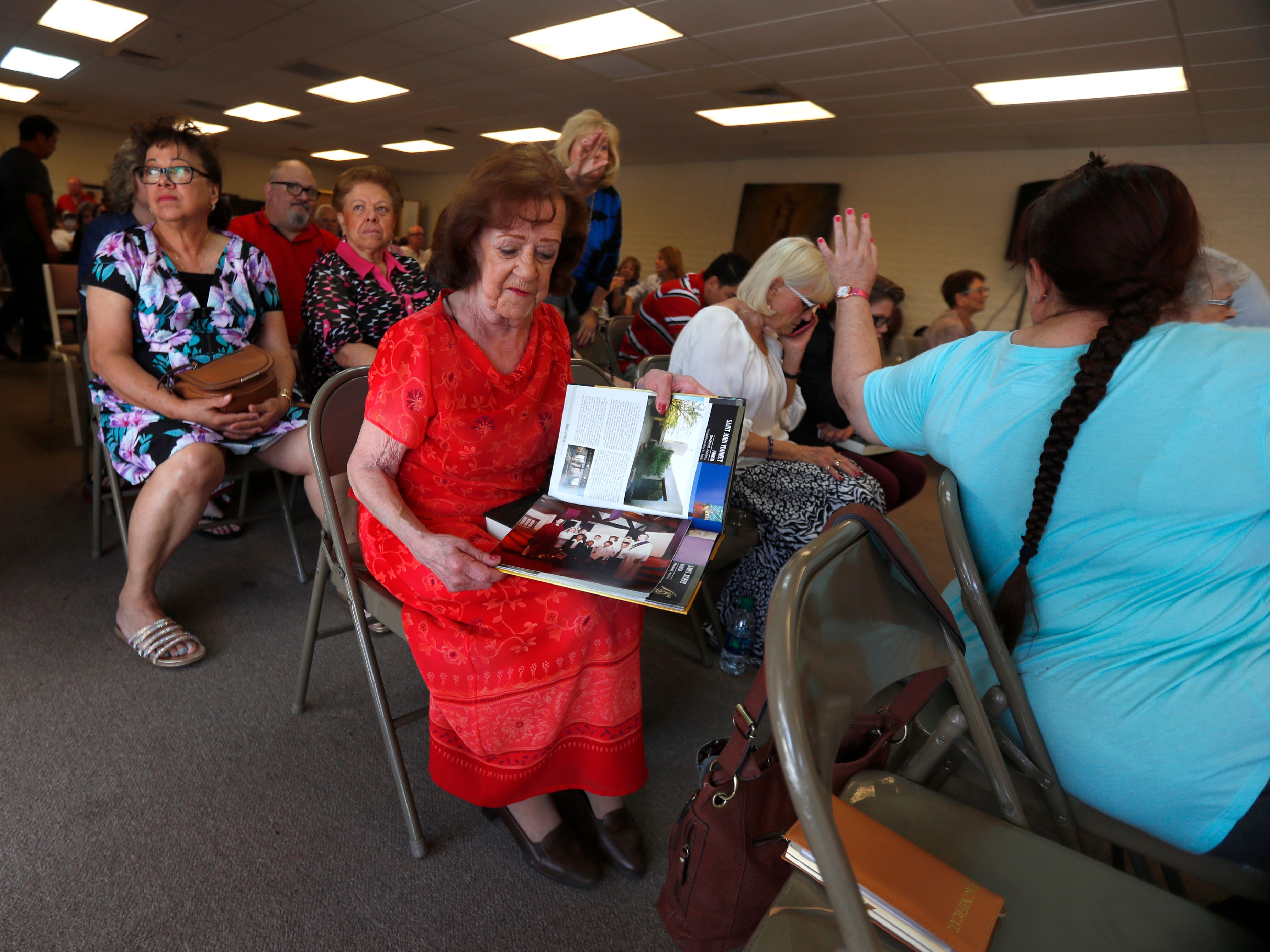Pat Kjelstad, a congregant since the beginning, shows pictures of what the church looked like before a fire inside Ascension Hall at St. Joseph Catholic Church in Phoenix on May 5, 2019.