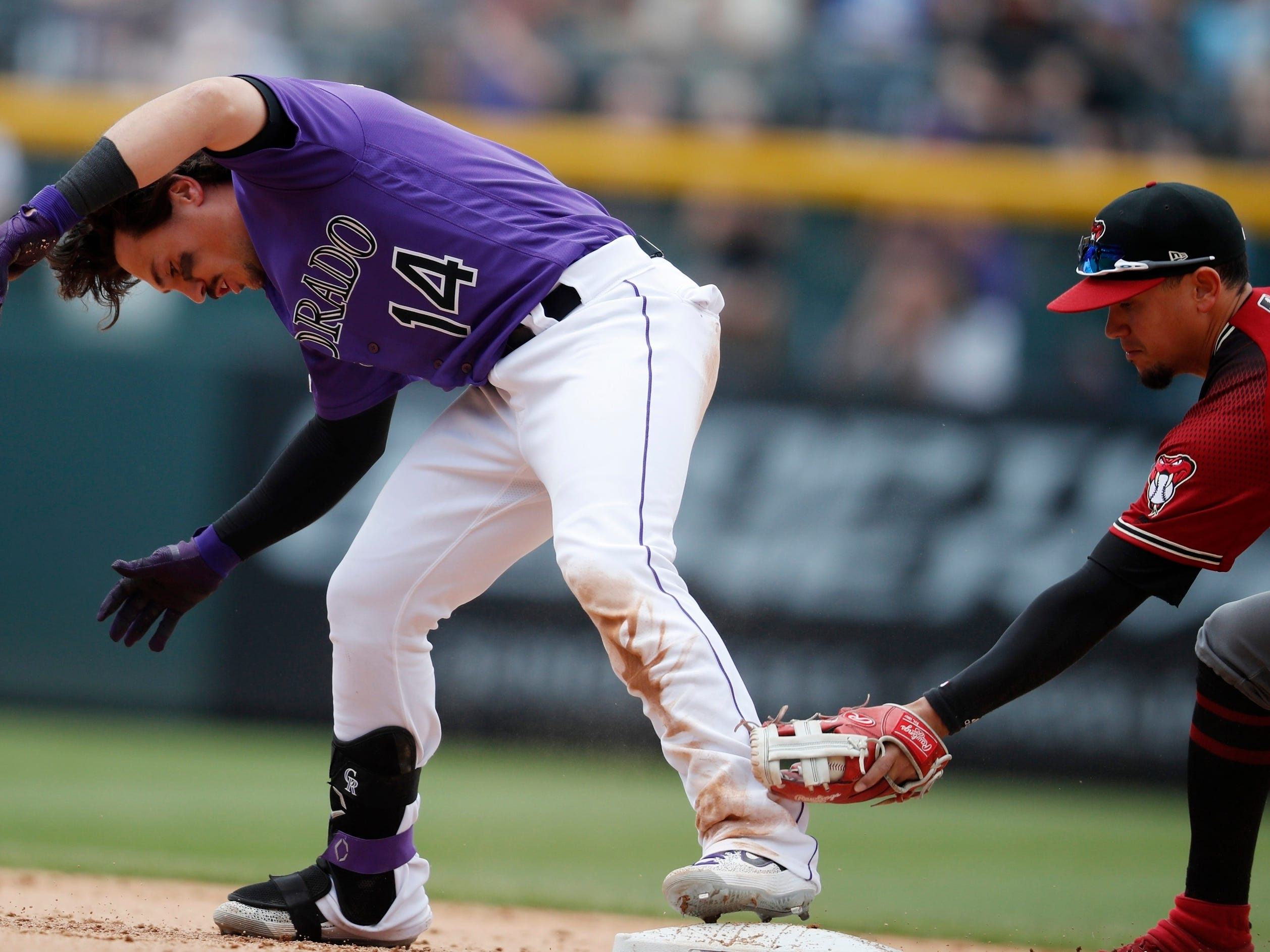Colorado Rockies' Tony Wolters, left, reaches second base with a double as Arizona Diamondbacks second baseman Ildemaro Vargas applies a late tag in the fifth inning of a baseball game Sunday, May 5, 2019, in Denver. (AP Photo/David Zalubowski)