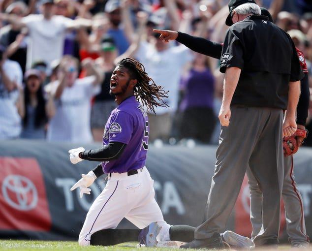 Colorado Rockies' Raimel Tapia reacts after hitting a triple to drive in three runs off Arizona Diamondbacks relief pitcher Archie Bradley in the eighth inning of a baseball game Sunday, May 5, 2019, in Denver. (AP Photo/David Zalubowski)