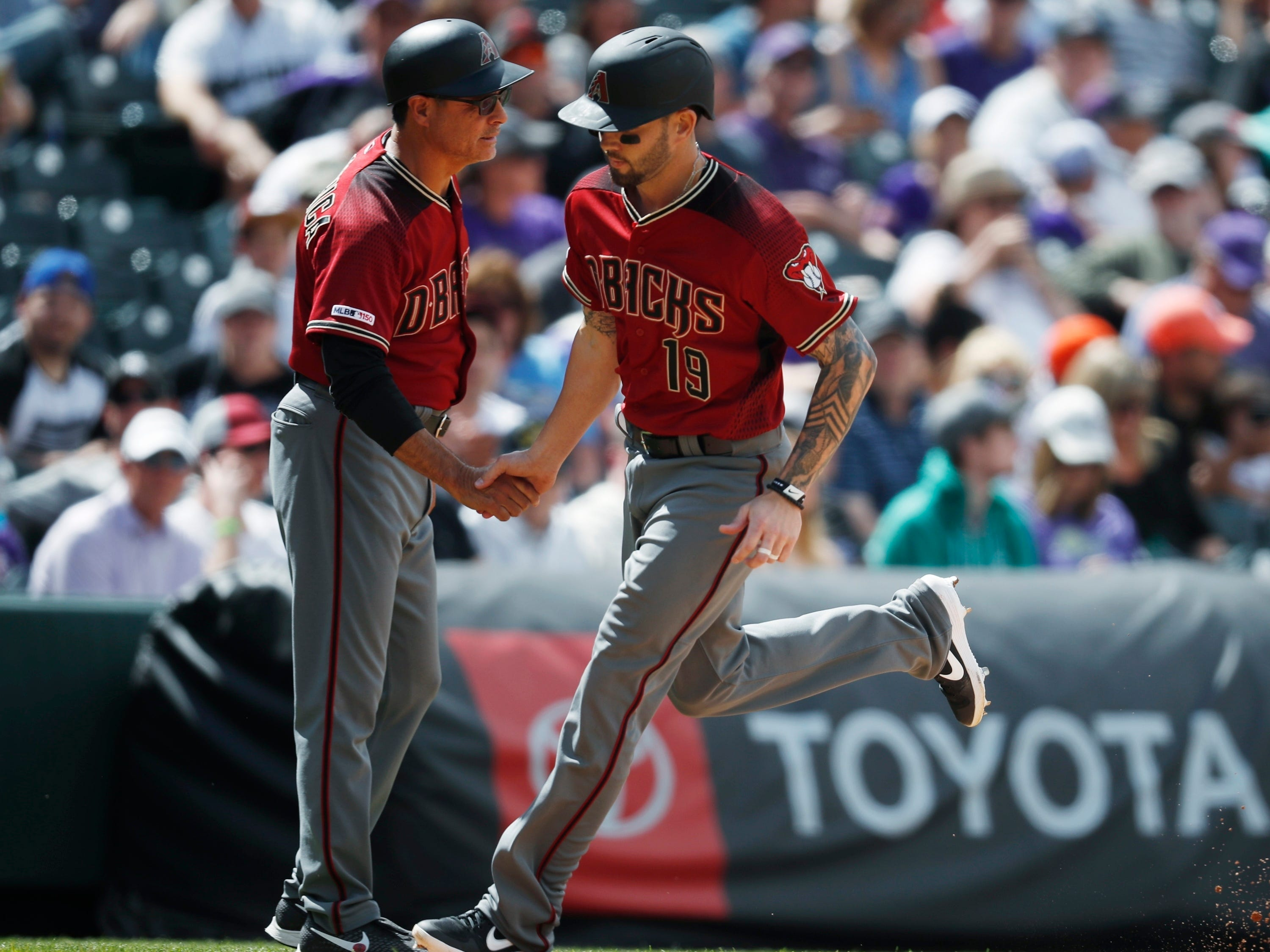 Arizona Diamondbacks third base coach Tony Perezchica, left, congratulates Blake Swihart as he circles the bases after hitting a two-run home run off Colorado Rockies starting pitcher German Marquez in the sixth inning of a baseball game Sunday, May 5, 2019, in Denver. (AP Photo/David Zalubowski)
