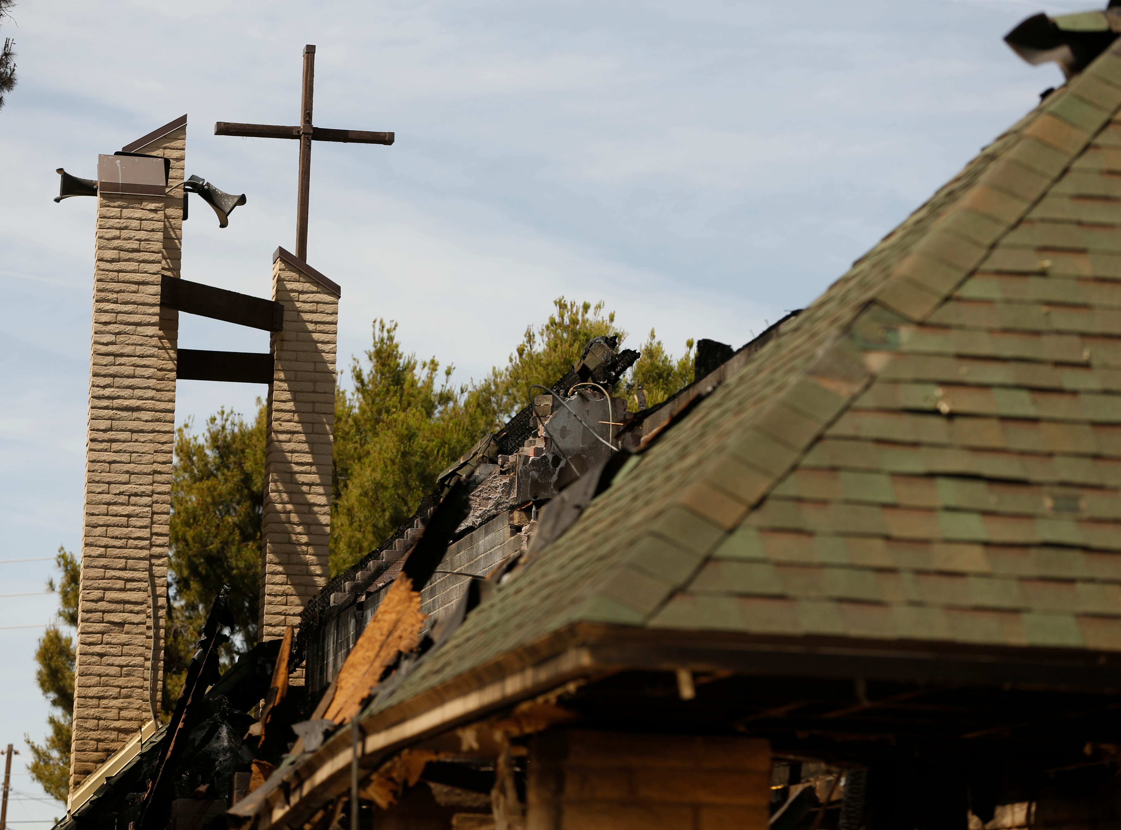 A cross sits above the damage from a fire at St. Joseph Catholic Church in Phoenix on May 5, 2019.