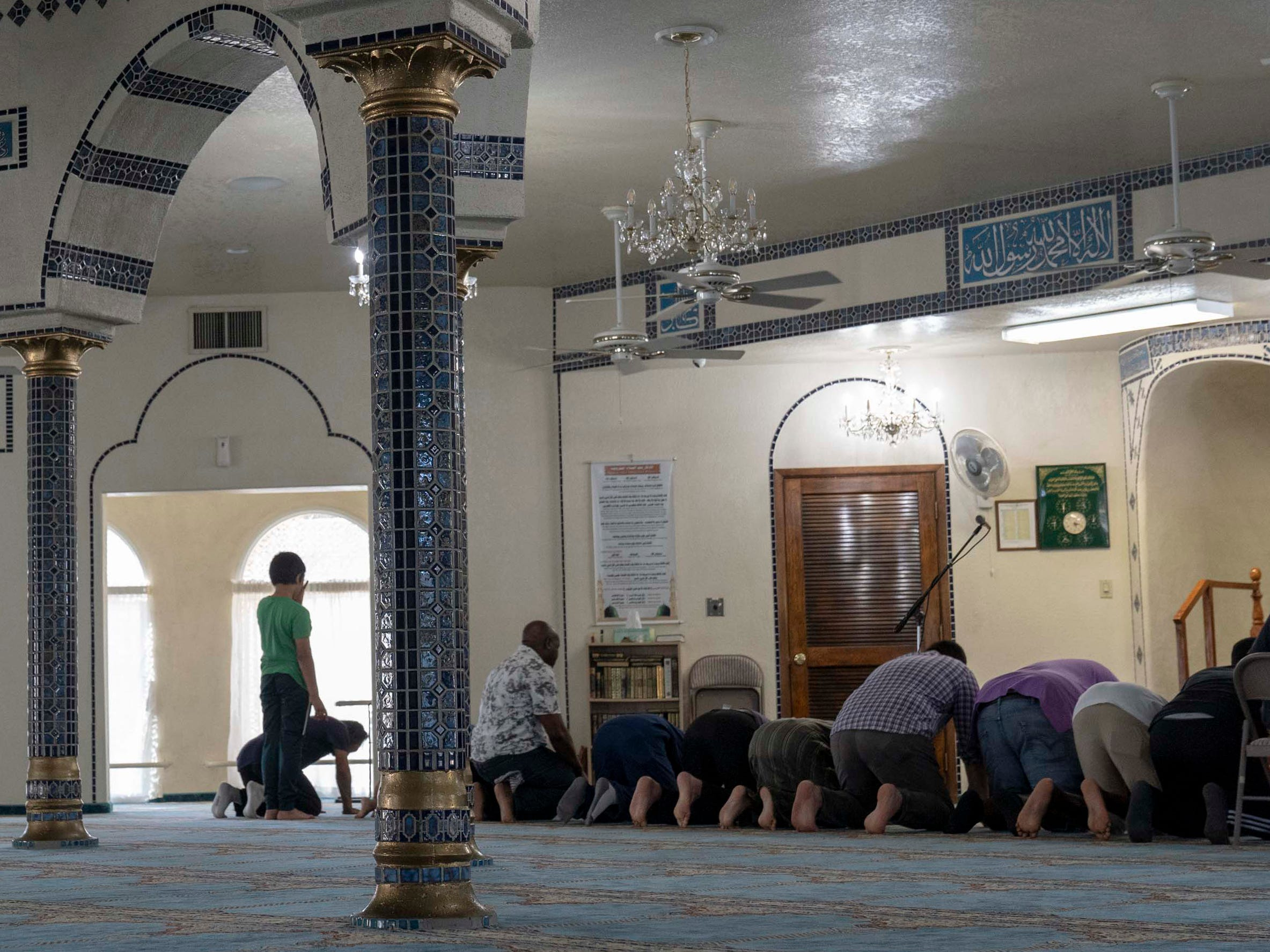Muslim men kneel during the evening prayer at Tempe Islamic Cultural Center.