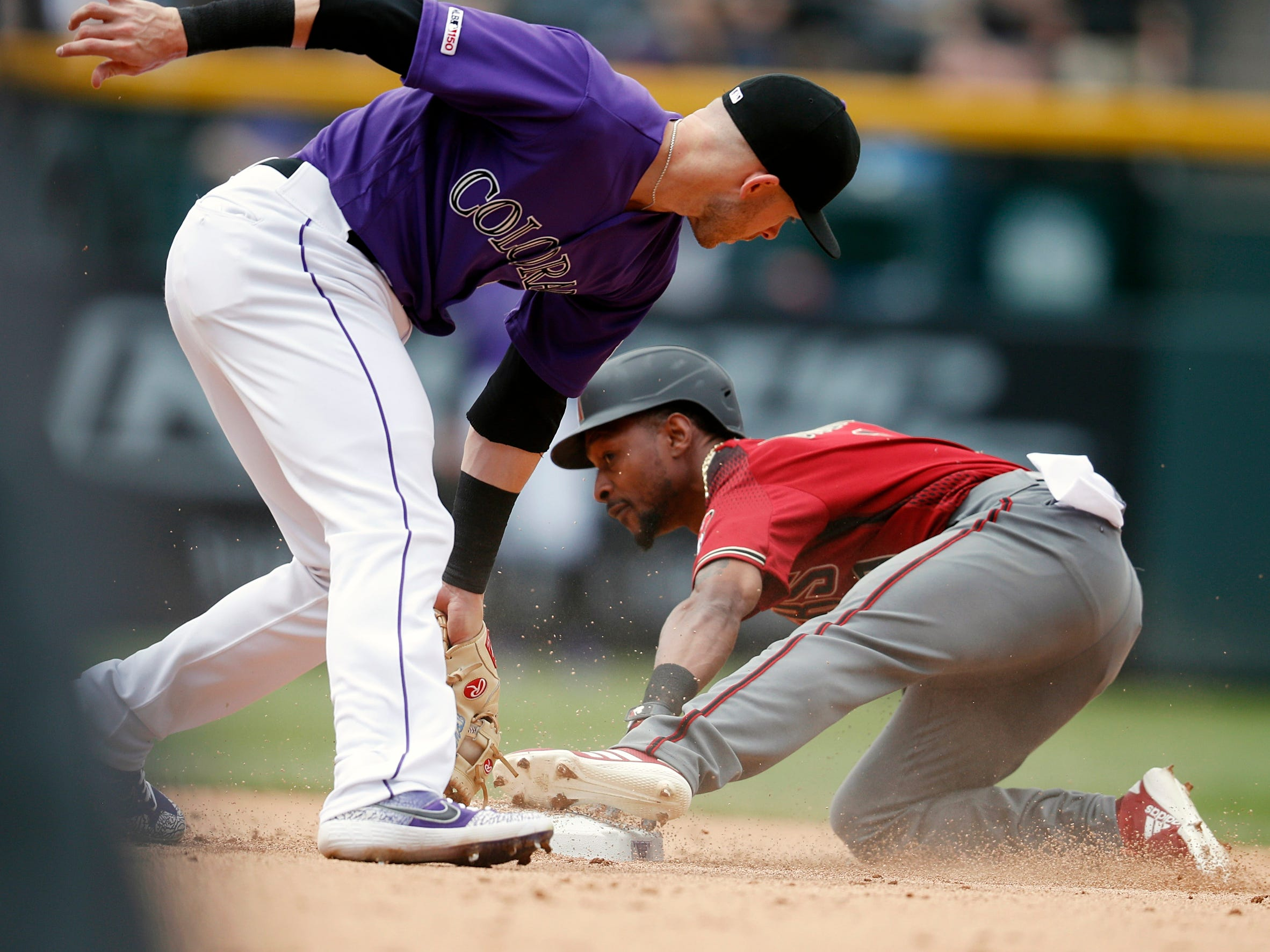 Colorado Rockies shortstop Trevor Story, left, applies a late tag as Arizona Diamondbacks' Jarrod Dyson steals second base in the fifth inning of a baseball game Sunday, May 5, 2019, in Denver. (AP Photo/David Zalubowski)