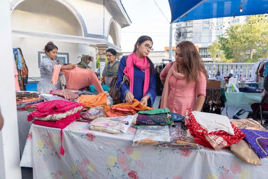 Rumey Alam, far left, from Simplicity Boutique sells clothes to Muslim community members for Ramadan at Tempe Islamic Cultural Center.