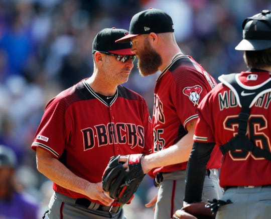 Arizona Diamondbacks manager Torey Lovullo, left, takes the ball from relief pitcher Archie Bradley as he is pulled from the mound after giving up a three-run triple to Colorado Rockies' Raimel Tapia in the eighth inning of a baseball game Sunday, May 5, 2019, in Denver. (AP Photo/David Zalubowski)