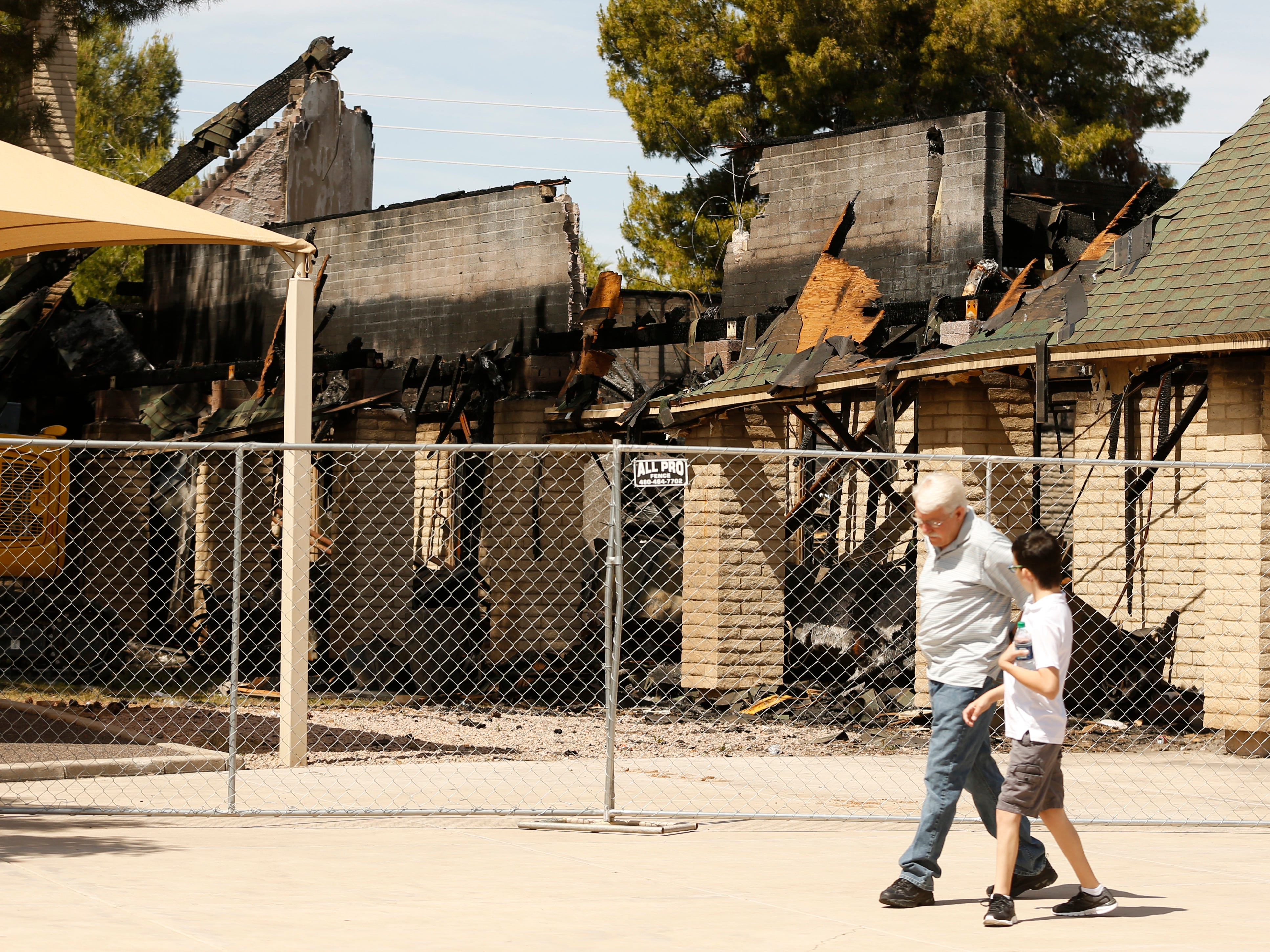 Congregants make their way past the main church after a fire at St. Joseph Catholic Church in Phoenix on May 5, 2019.