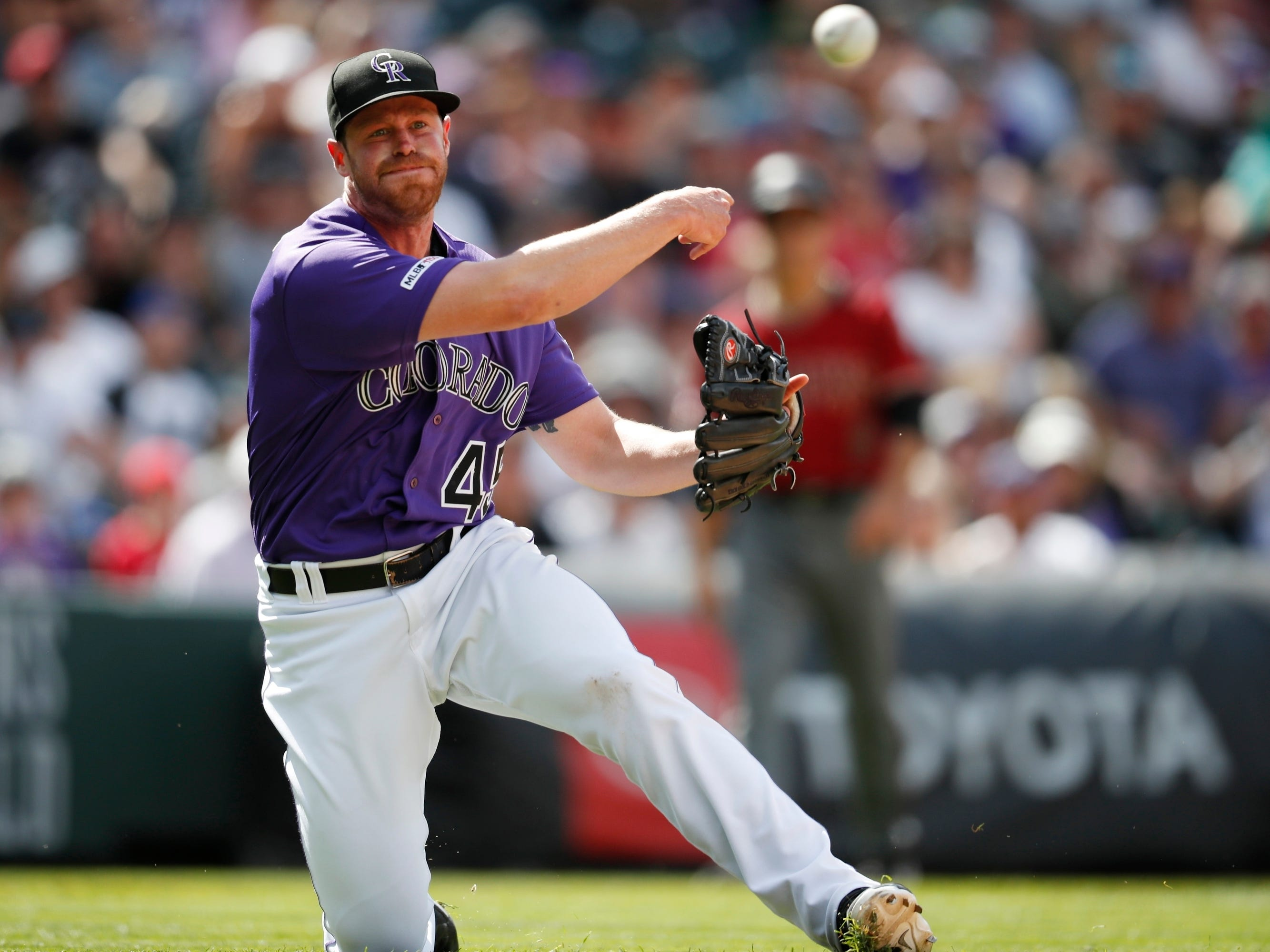 Colorado Rockies relief pitcher Scott Oberg throws to first base to put out Arizona Diamondbacks' John Ryan Murphy in the eighth inning of a baseball game Sunday, May 5, 2019, in Denver. (AP Photo/David Zalubowski)