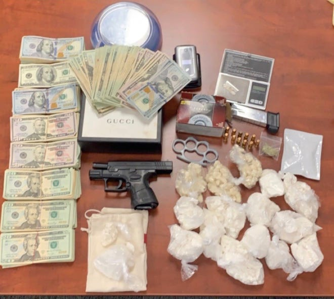 Items that were seized from Johnny Jones' residence, including cocaine and crack cocaine, sit on display.