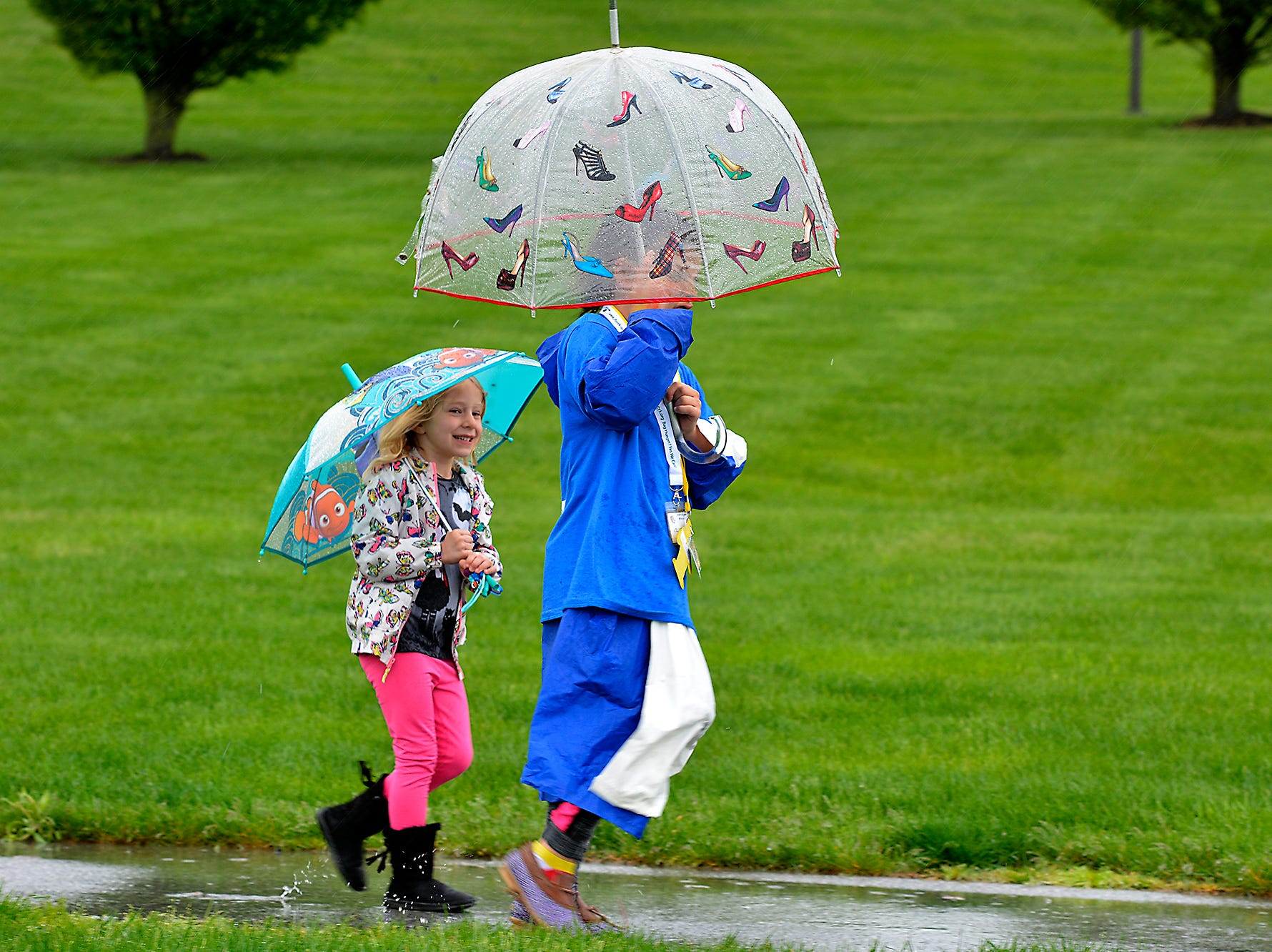 Hannah Kohr, 5 at left, and Juliet Lewin, 10, splash through a puddle while taking part in the Jewish Family Services (JFS) 18th annual Hustle 4 Hunger Walkathon at Springettsbury Township Park, Sunday, May 5, 2019.