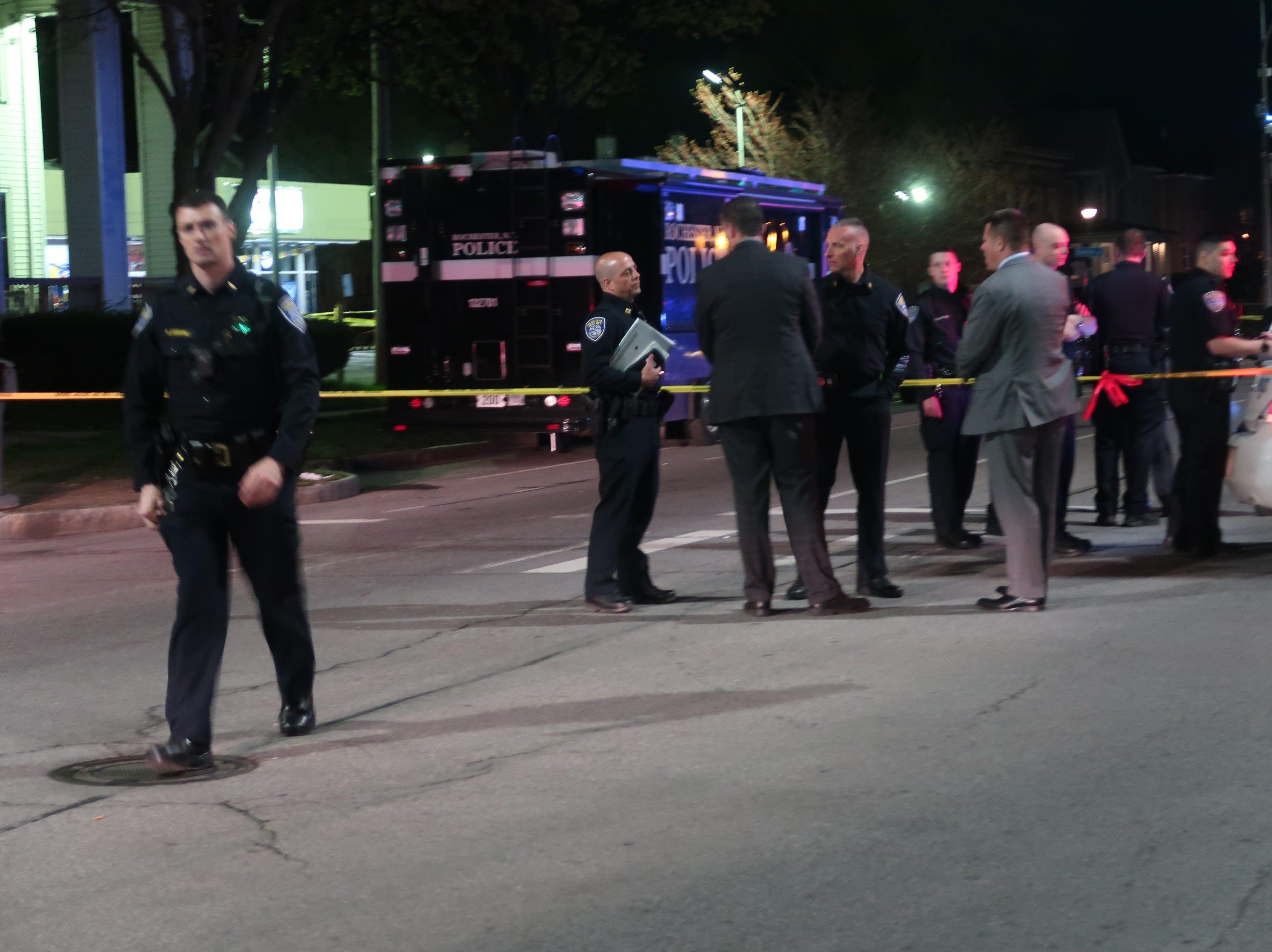 Lt. Brian Marone, left, walks away from the crime scene late Saturday night on Dewey Avenue.