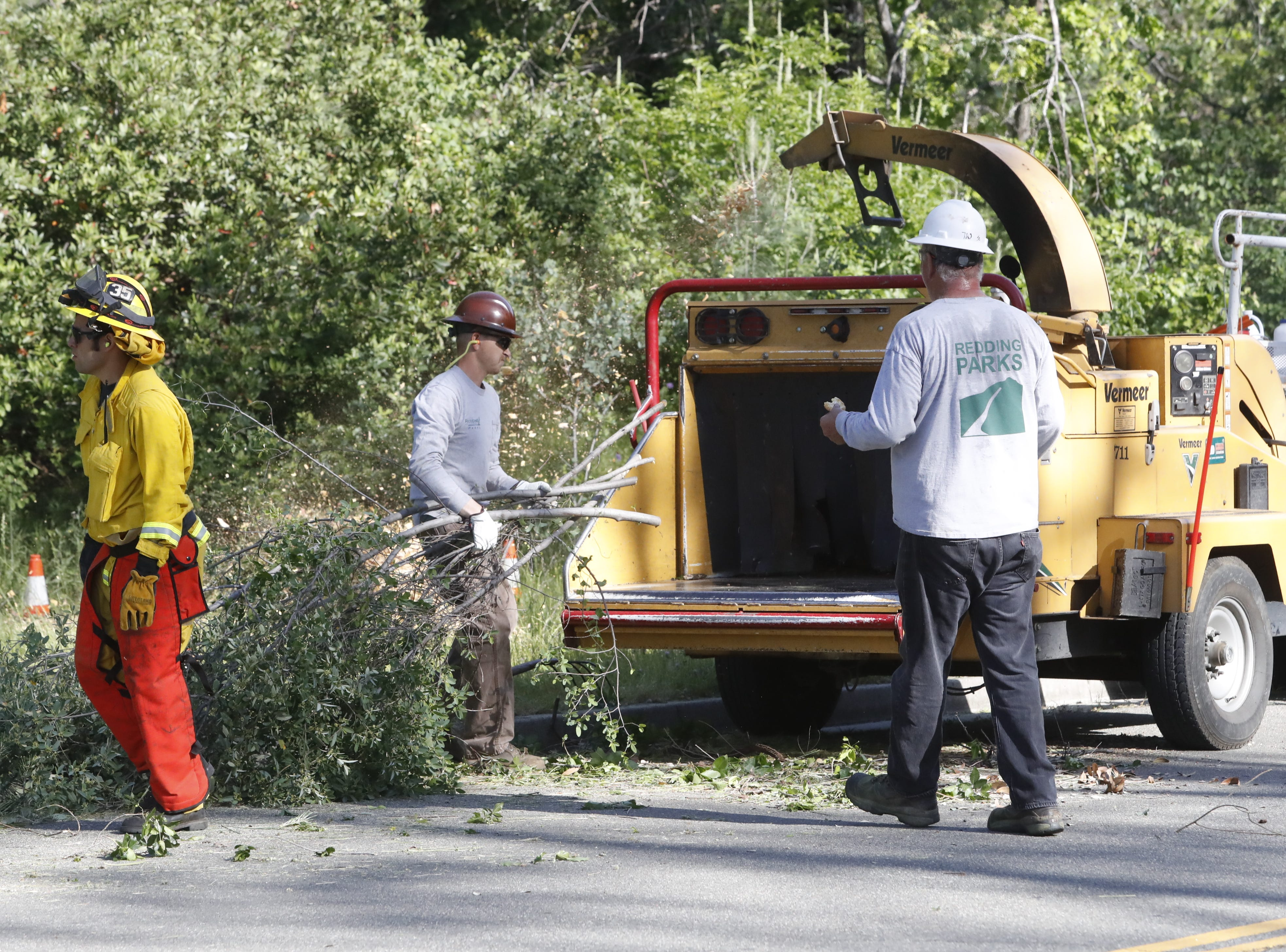 City workers and citizen volunteers hit the hillsides along Blazingwood Drive near the Country Heights subdivision to clear overgrown grass and brush in a defensible-space operation for Wildfire Community Preparedness Day.