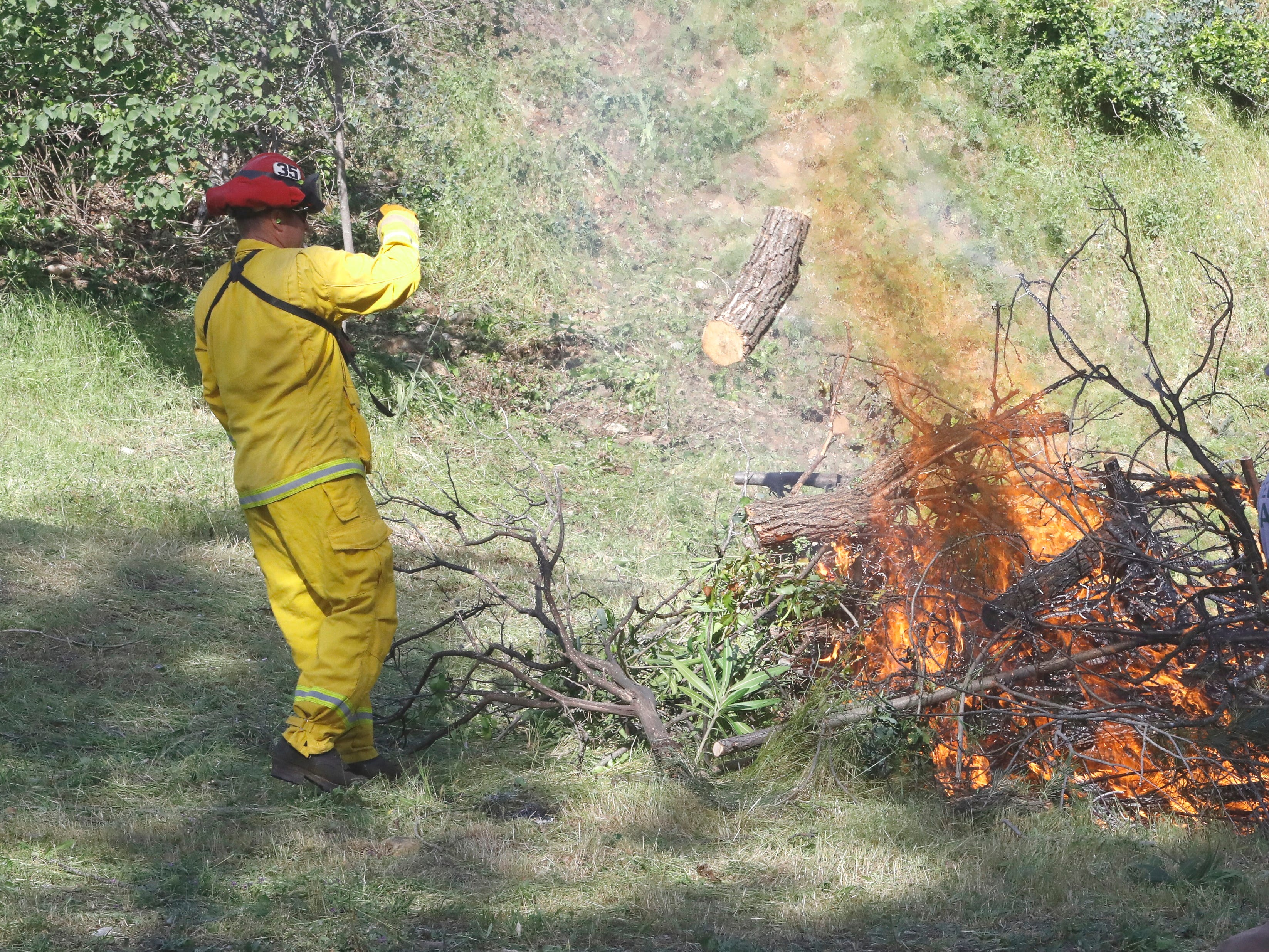 A Redding firefighter tosses wood into a burn pile during a defensible-space operation along Blazingwood Drive on Saturday, May 4, 2019.