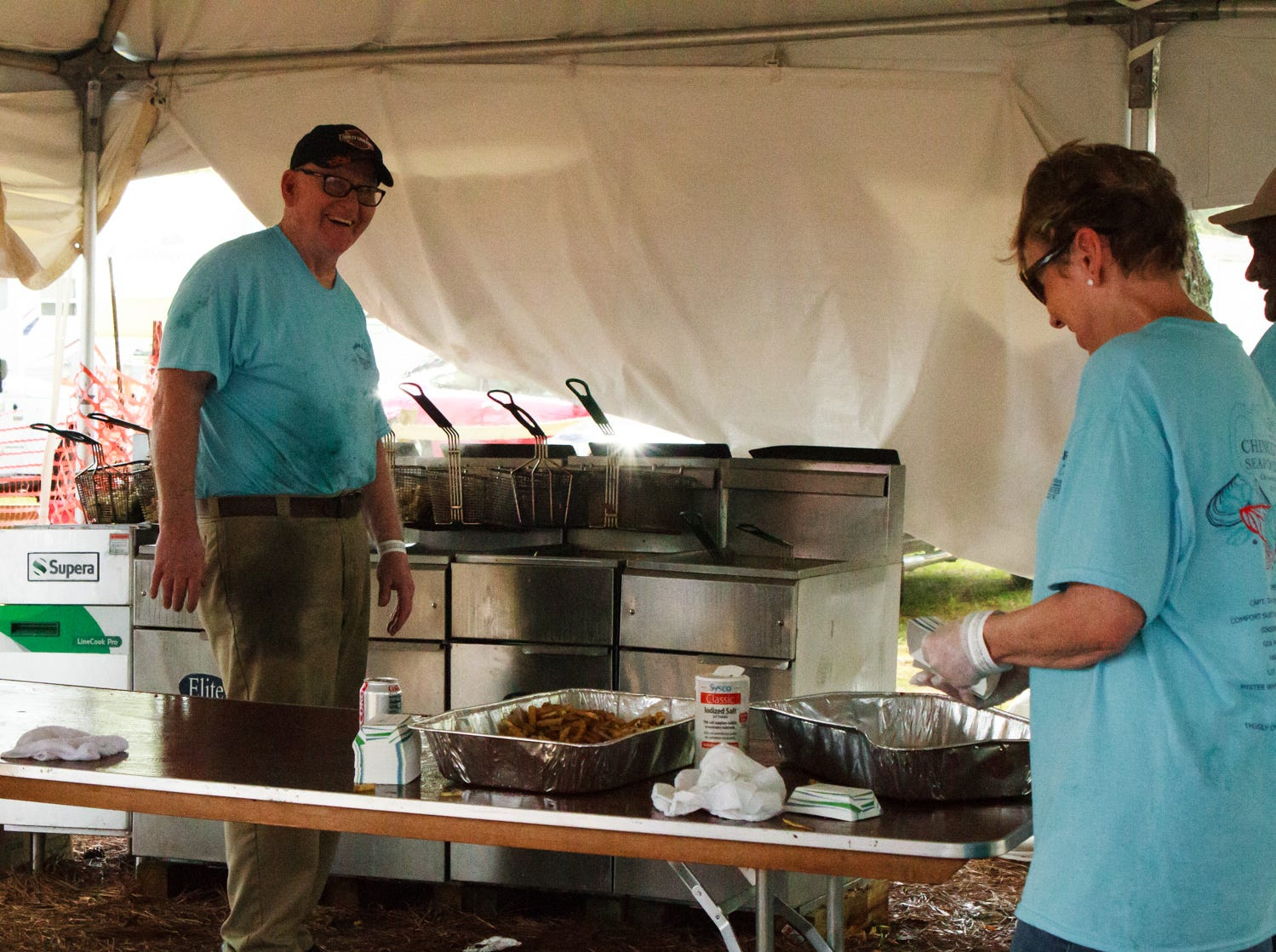 Charlene Jacob of Accomac, VA and Ernest Ruediger of Onancock, VA take time inbetween preparing French fries to share jokes on Saturday, May 4, 2019 at the Chincoteague Seafood Festival in Chincoteague, VA.