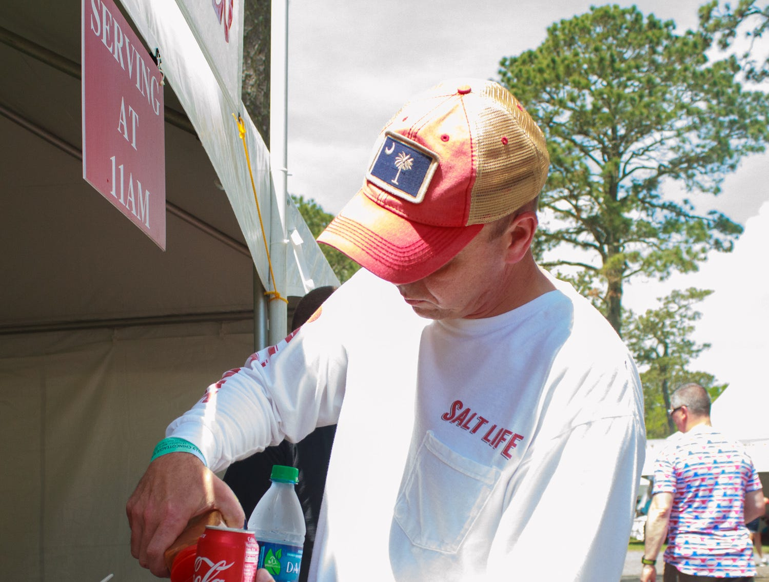 James Sparks prepares a cup of Old Bay seasoning to sit down and eat with on Saturday, May 4, 2019 at the Chincoteague Seafood Festival in Chincoteague, Virginia