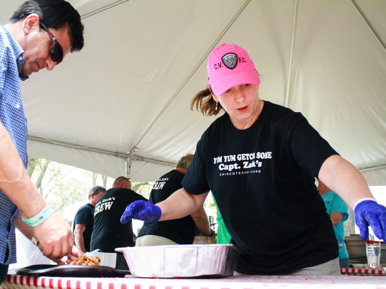 Beverly Bowden of Chincoteague, VA serves Mario Alvarez of Long Island, NY on Saturday, May 4, 2019 at the Chincoteague Seafood Festival in Chincoteague, VA.
