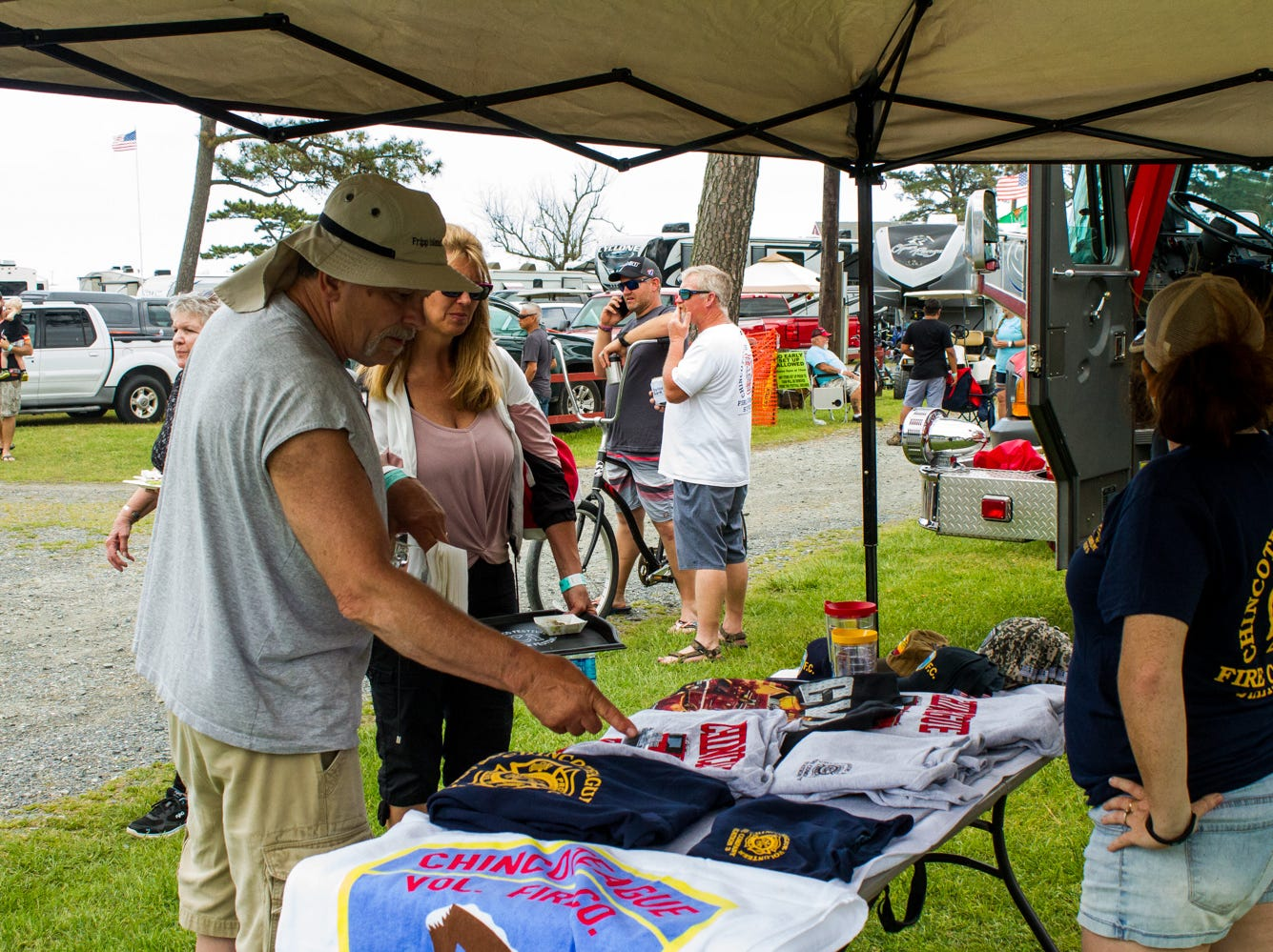 Allen and Tammy Hoeffner of Strasburg, CO inspect t-shirts for sale by the Chincoteague Volunteer Fire Department on Saturday, May 4, 2019 at the Chincoteague Seafood Festival in Chincoteague, VA.