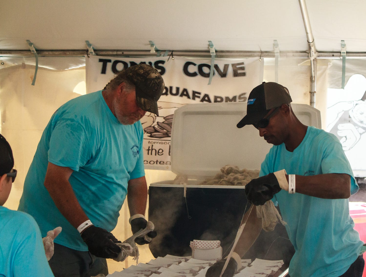 Members of Tom's Cove Aquaforms prepare clams for festival attendees on Saturday, May 4, 2019 at the Chincoteague Seafood Festival in Chincoteague, Virginia.