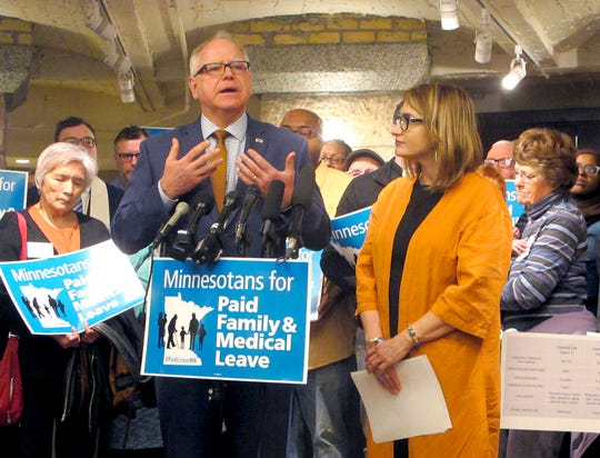 In this Friday, May 3, photo, Minnesota Gov. Tim Walz speaks at a news conference in the state Capitol in St. Paule. Listening to the governor is Lt. Gov. Peggy Flanagan.