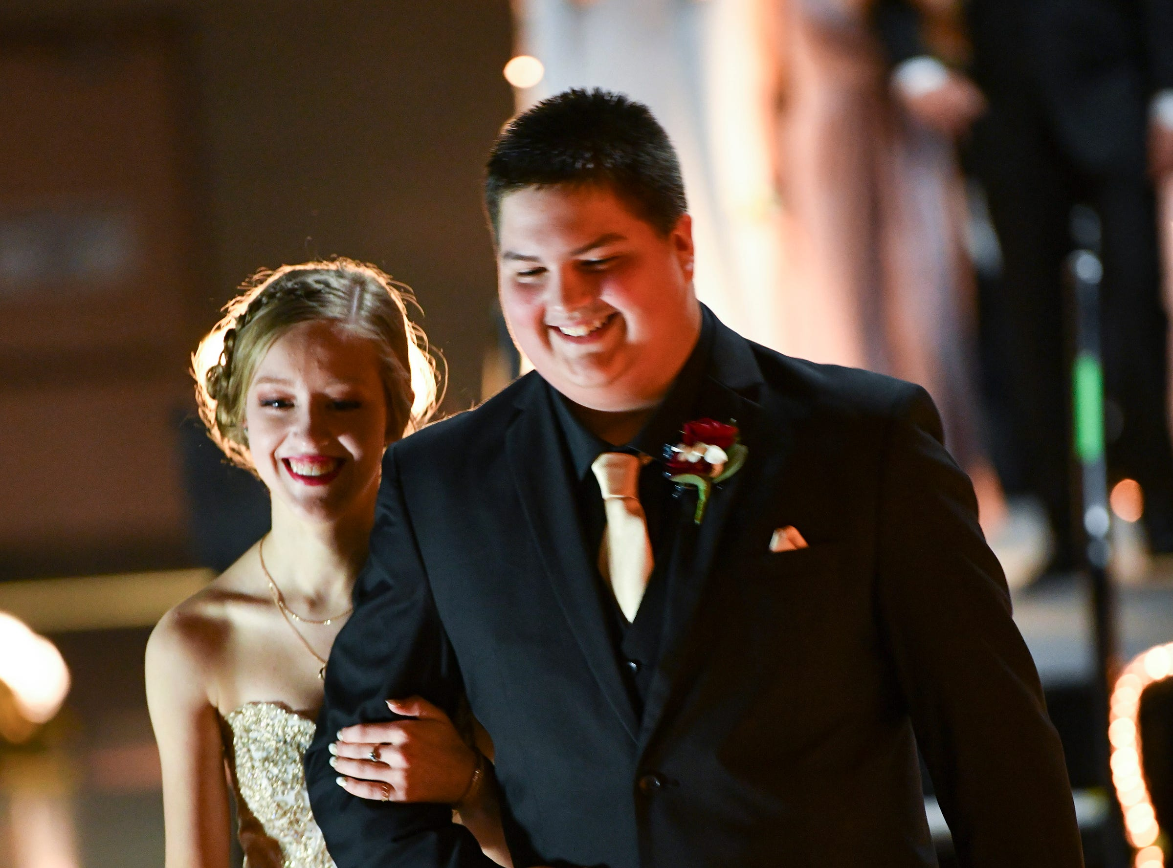 Couples smile while walking the grand march route during Sartell High School's prom Saturday, May 4, at the River's Edge Convention Center in St. Cloud.