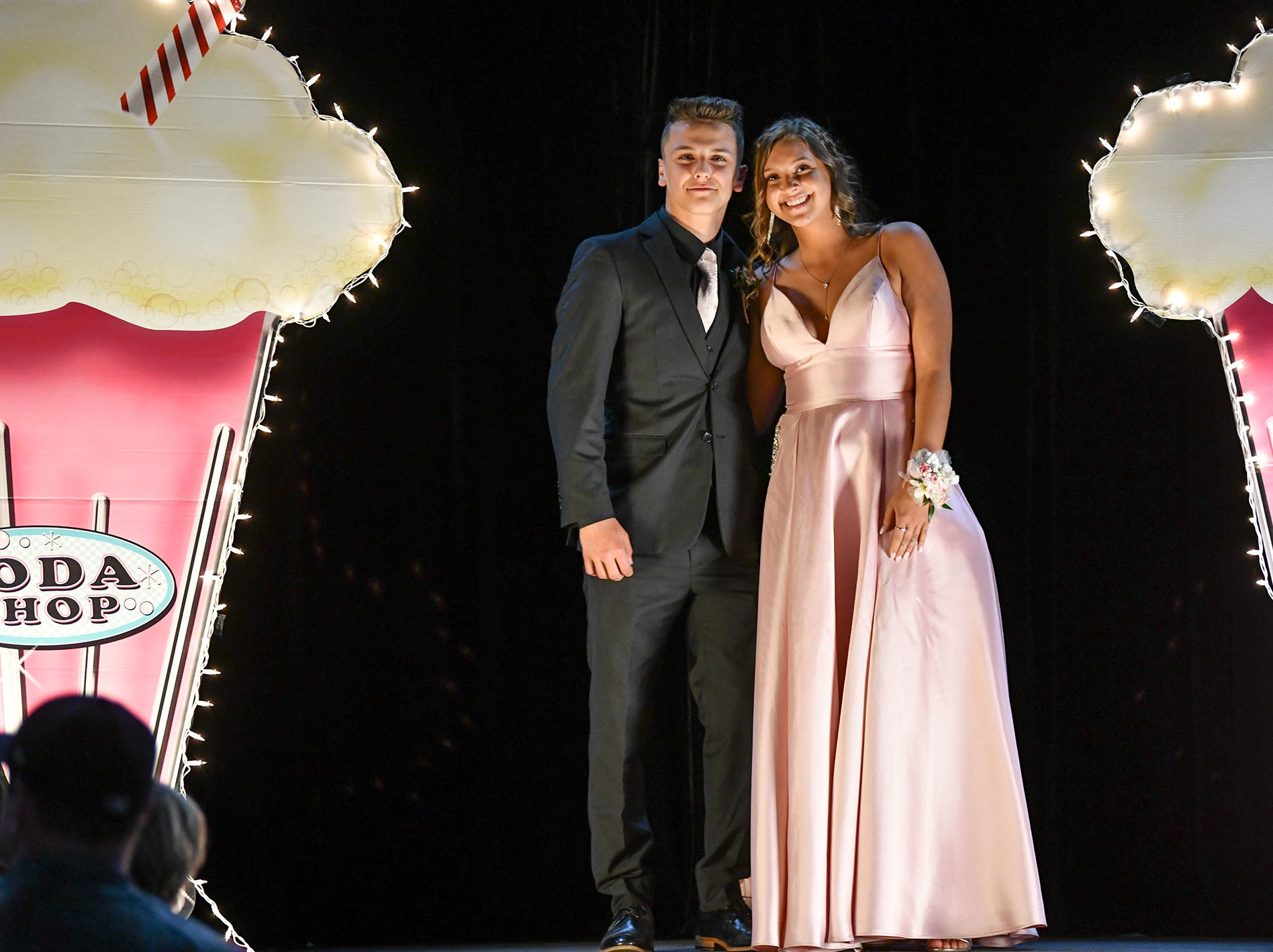 Promgoers smile on stage during Sartell High School's prom grand march Saturday, May 4, at the River's Edge Convention Center in St. Cloud.