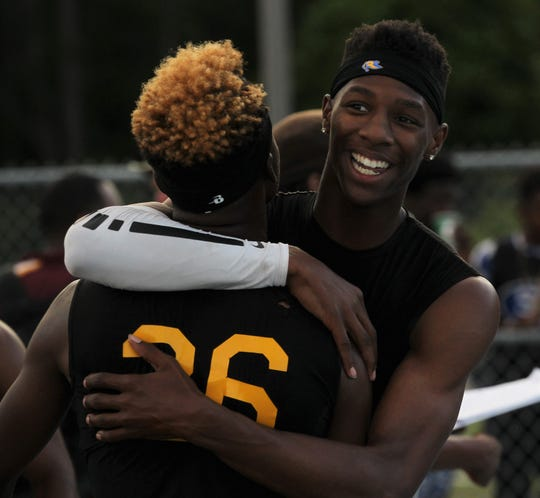 Chris Robinson hugs Jabari Bryant after Rickards' boys 4x400 team captured a gold medal, leading the Raiders to a Class 2A state runner-up finish at the FHSAA Track and Field State Championships on May 3 and 4, 2019.