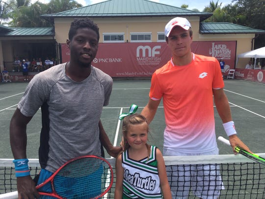 Sekou Bangoura of Bradenton, Florida (left) poses with Dmitry Popko of Kazakhstan and the ceremonial coin flipper Taylor from the Sea Turtles cheer squad from Sebastian, Florida, one of the Mardy Fish Children's Foundation partner programs.