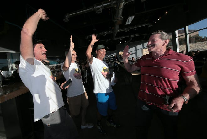 Lost Dog Trail supporters, including Brent Sanders, left, and Rick Bonart, right, celebrate Saturday, May 4, 2019, after seeing they were ahead in early voting with a commanding lead in saving 1,000 acres of natural space in Northwest El Paso which includes the trailhead for Lost Dog Trail.