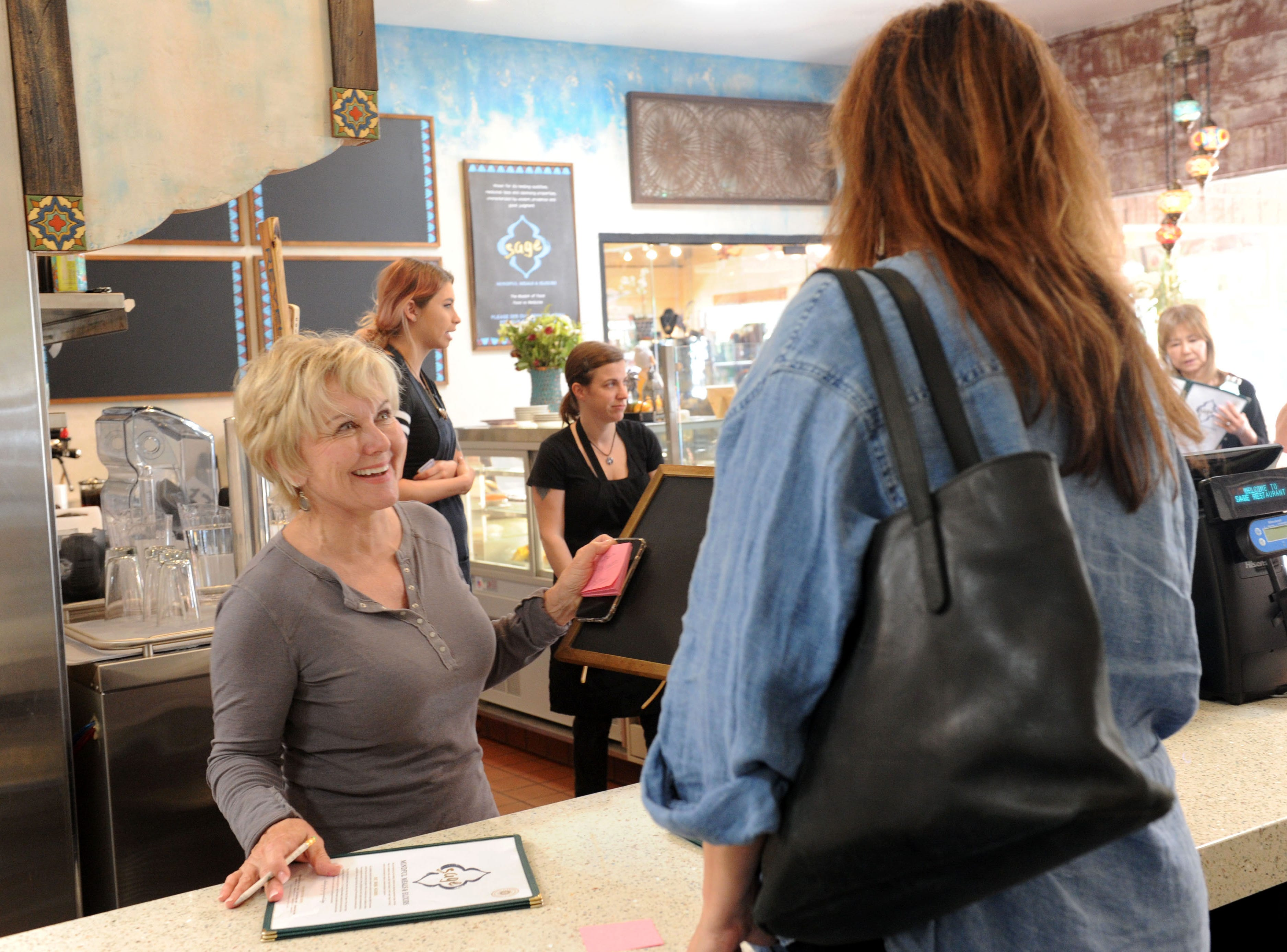 Mary Tradeau, owner of Sage Mindful Meals and Elixirs in Ojai, talks with customer Melanie Hilgers.