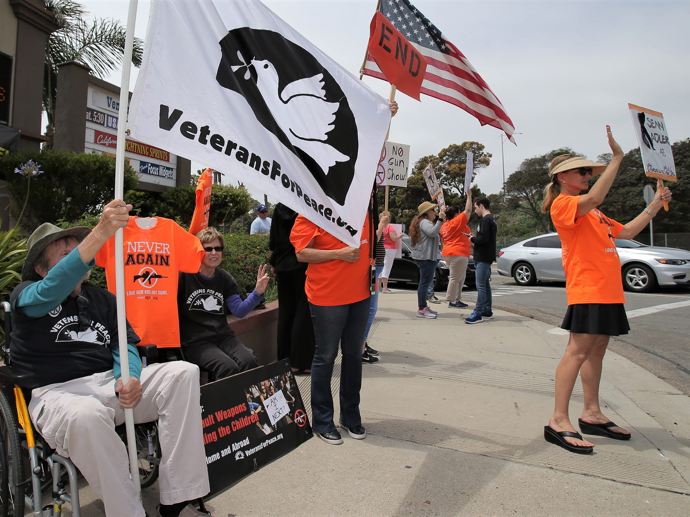 From left are gun-control supporters Carl Smith; his wife, Sheila; Julie Diaz, behind flag; and Anitra Evans. They were demonstrating Saturday during the Crossroads of the West Gun Show at the Ventura County Fairgrounds. About 40 people showed up for the protest. Diaz and Evans said they knew people who were killed in the Borderline shooting.